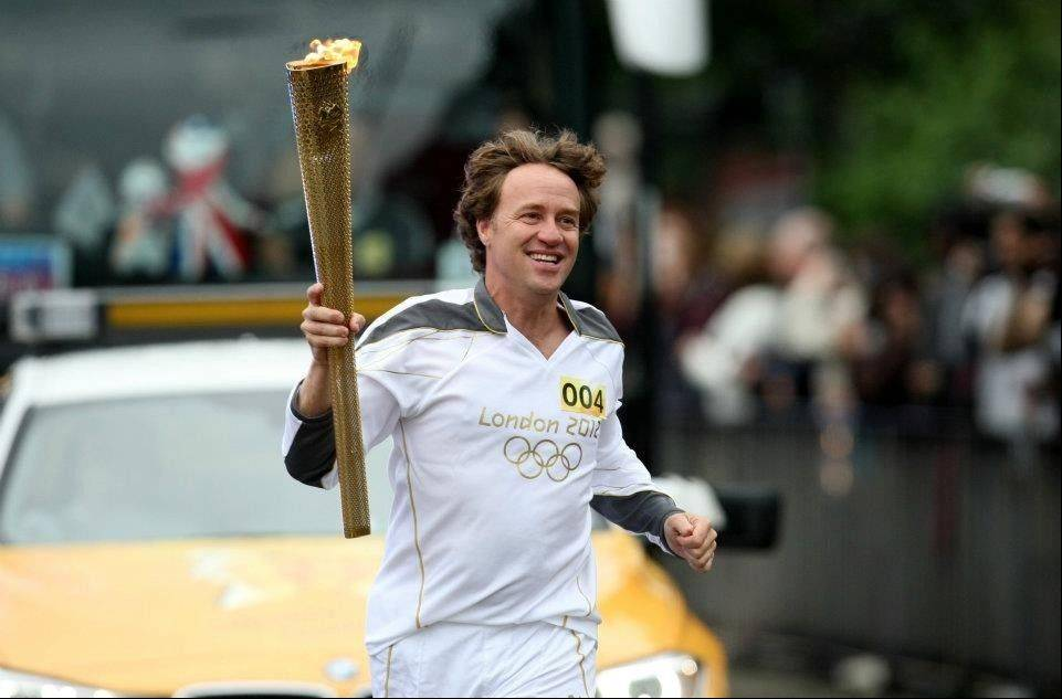 Abt Electronics co-President Mike Abt with the Olympic torch runs on the streets of Luton, England.