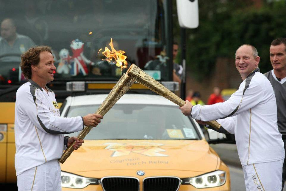 Abt Electronics co-President Mike Abt transfers the Olympic flame on Dunstable Road in Luton, England.