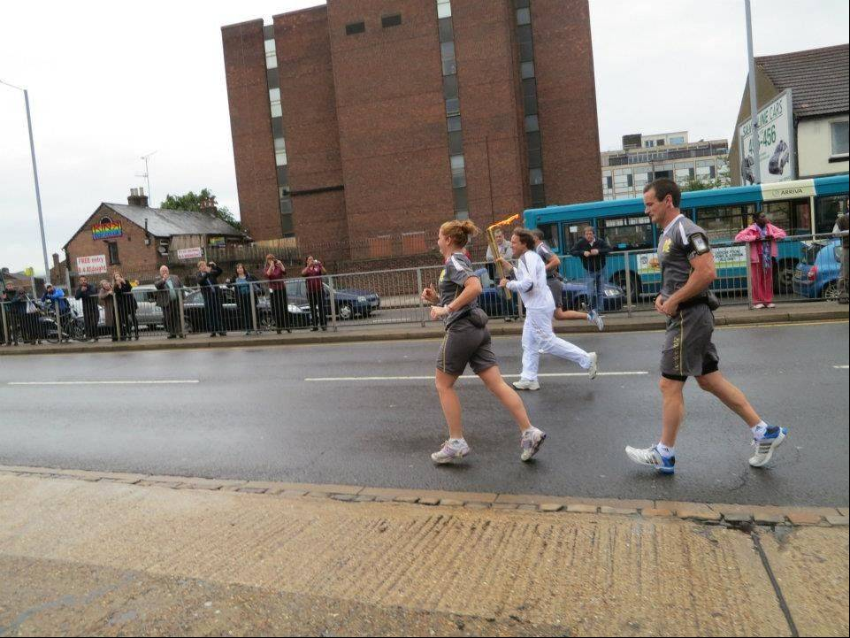 Abt Electronics co-President Mike Abt runs during his 300-meter segment down Chapel Viaduct in Luton, England. The Olympic torch is about 2 feet 6 inches and weighs 2.2 pounds.