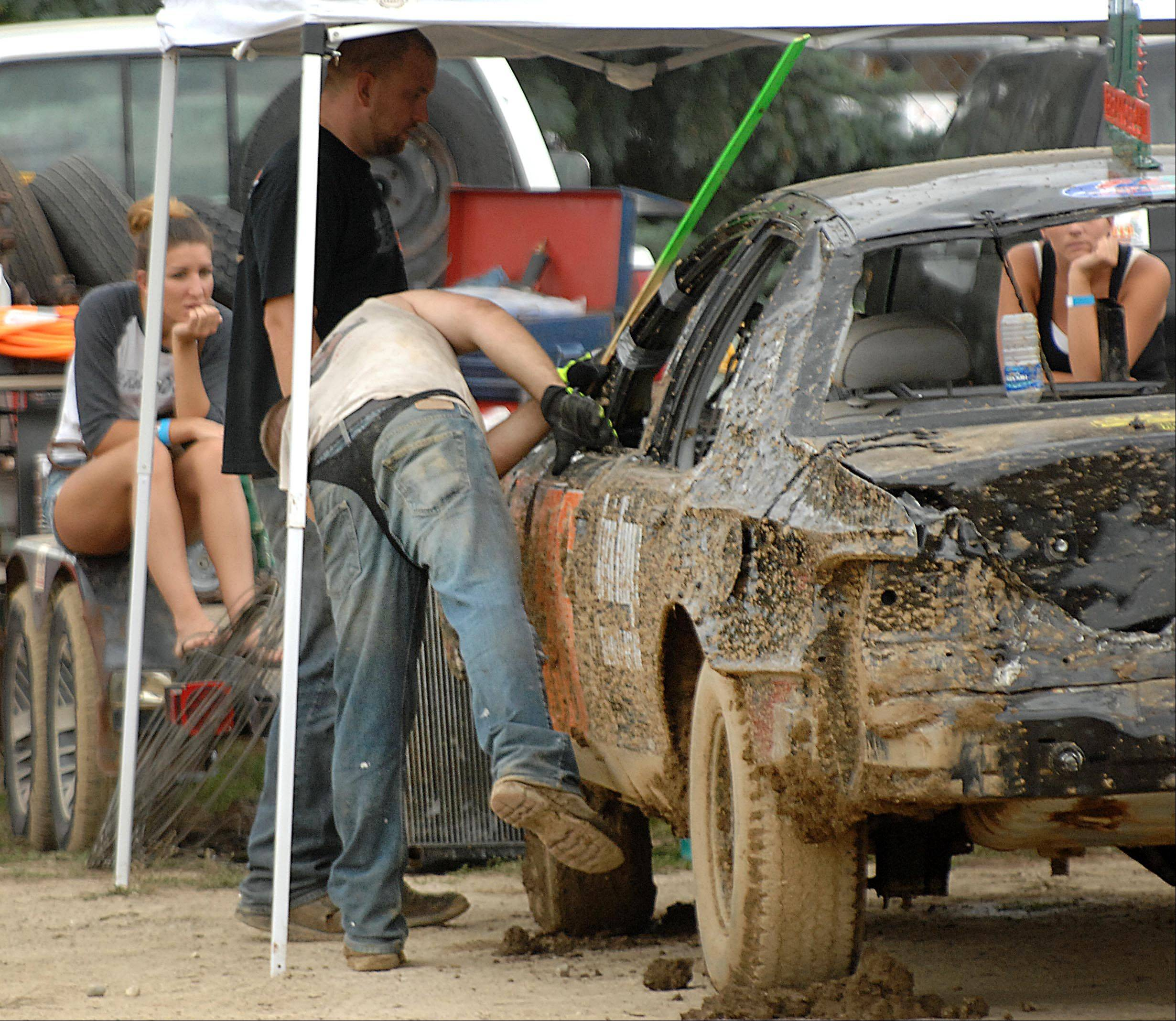 Wearing a thong over his jeans after losing a bet, Michael Brancecum of St. Charles works on his car after qualifying for the Championship round of the Demolition Derby at the Kane County Fair Sunday in St. Charles.