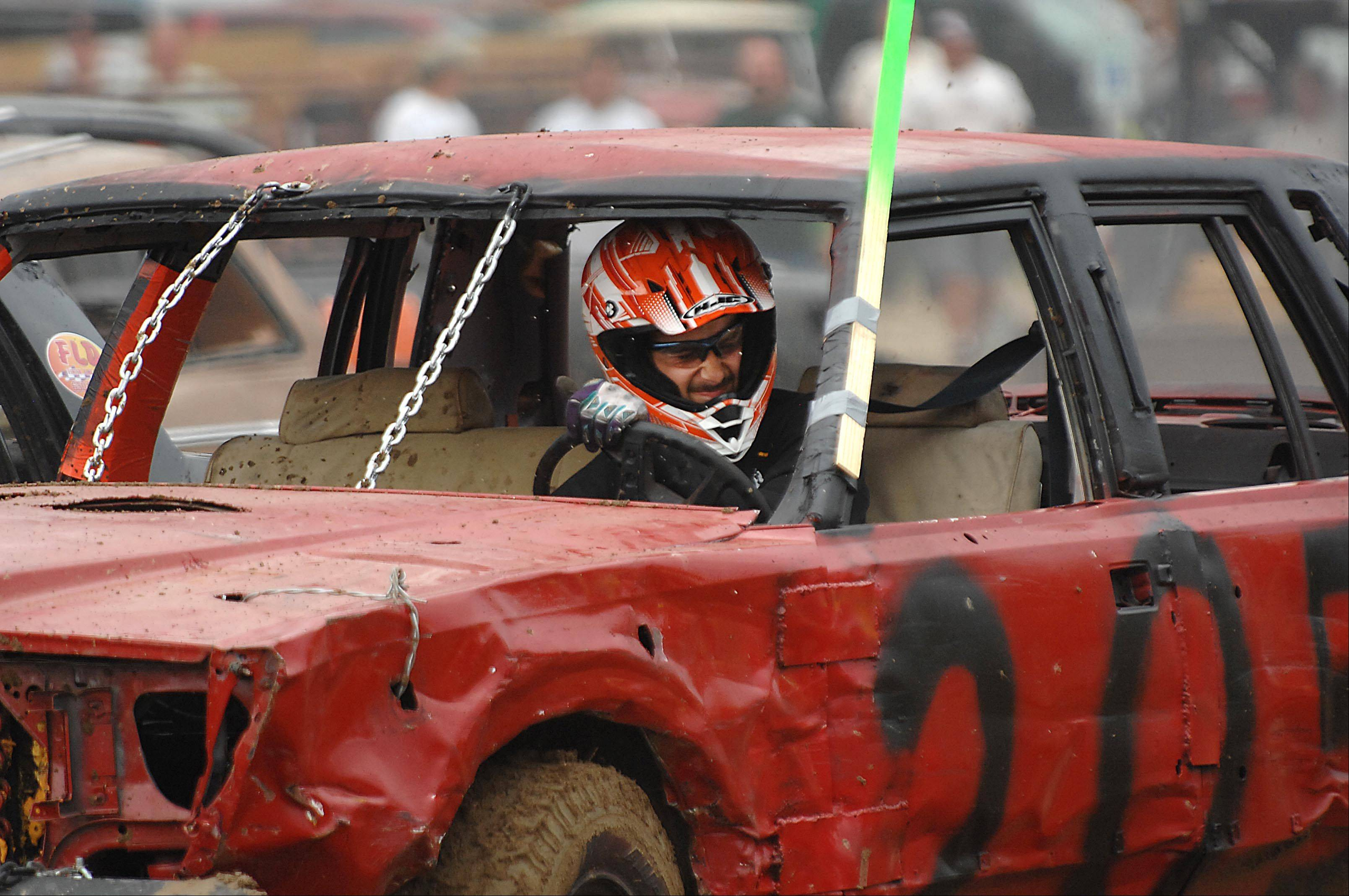 Sam Barris of Lake Zurich grimaces as he is hit during the Demolition Derby at the Kane County Fair Sunday in St. Charles.