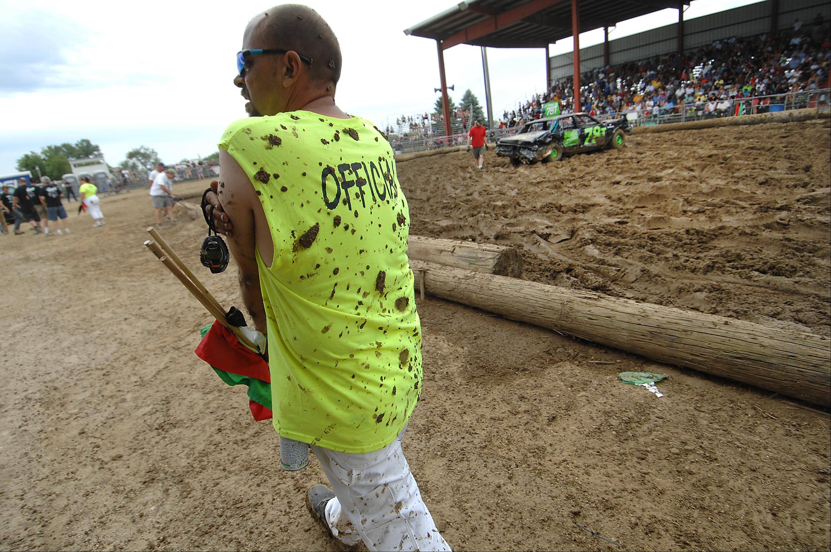 A mud-splattered official walks past the arena between heats of the Demolition Derby at the Kane County Fair Sunday in St. Charles.