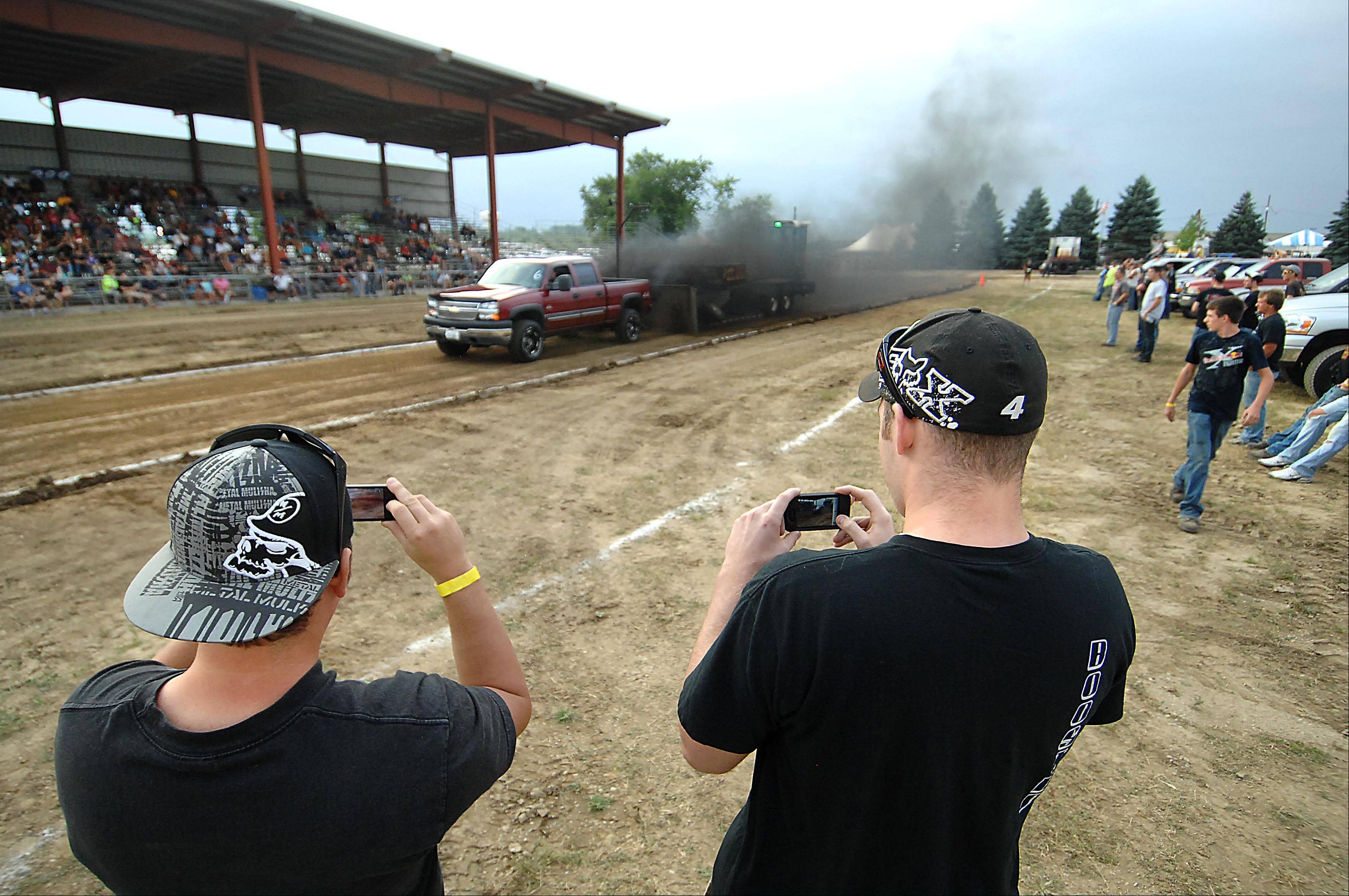 A diesel pickup blows black smoke as it pulls the sled down the 260-foot track during a Truck Pull competition at the Kane County Fair Thursday in St. Charles.
