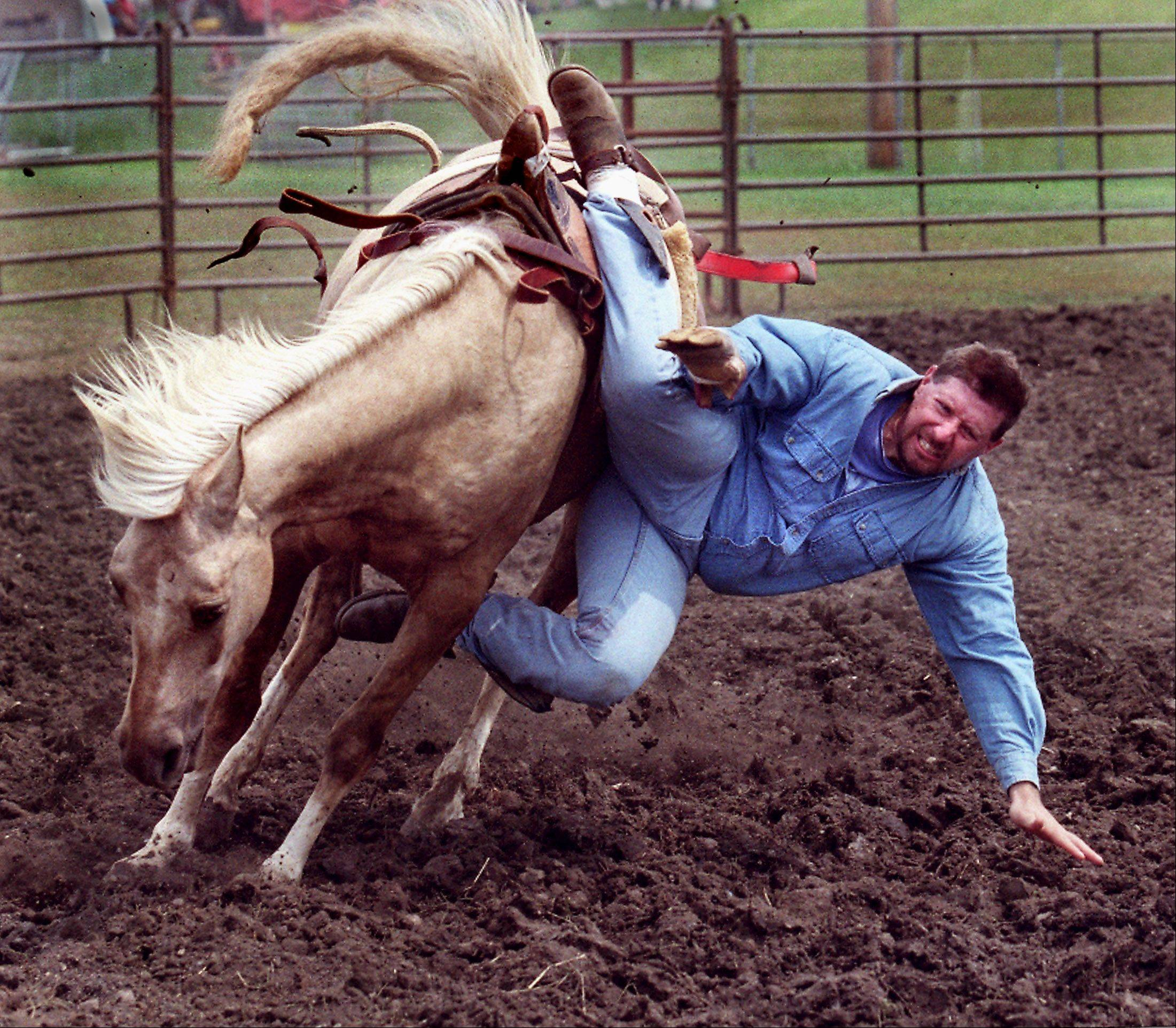 "2003: Cowboy Todd Guynn takes a tumble off Yellow Mare during the Lazy ""C"" Rodeo."