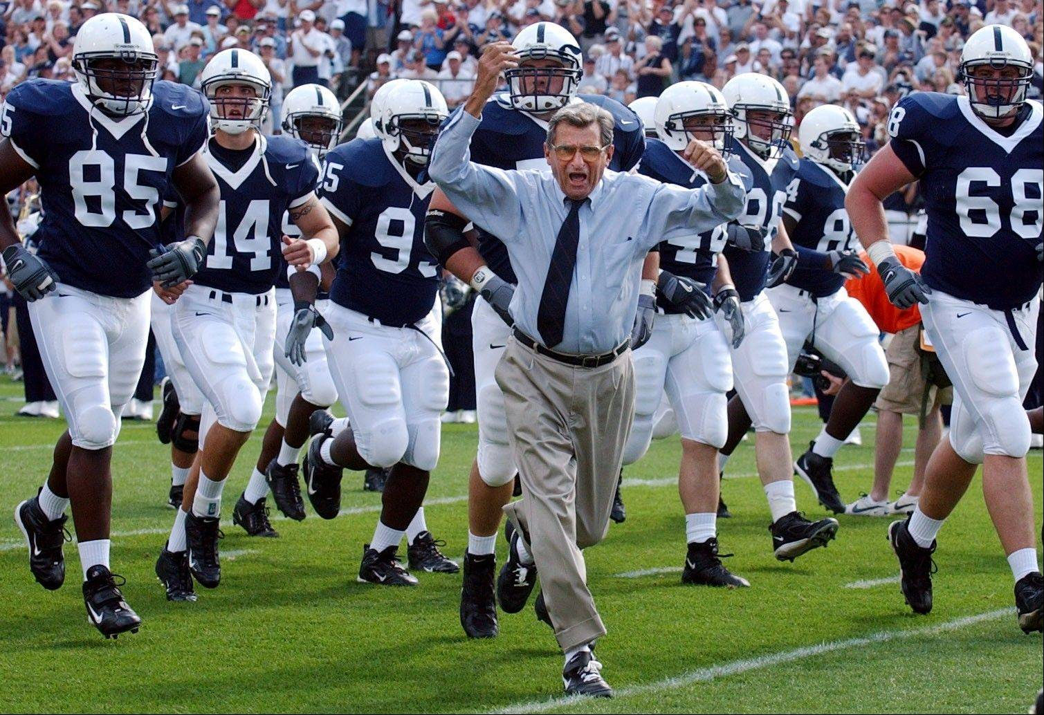 In this Sept. 4, 2004 file photo, Penn State coach Joe Paterno leads his team onto the field before an NCAA college football game against Akron in State College, Pa. The legendary college football coach was disgraced for concealing child sex abuse allegations against a retired assistant coach for years to avoid bad publicity.
