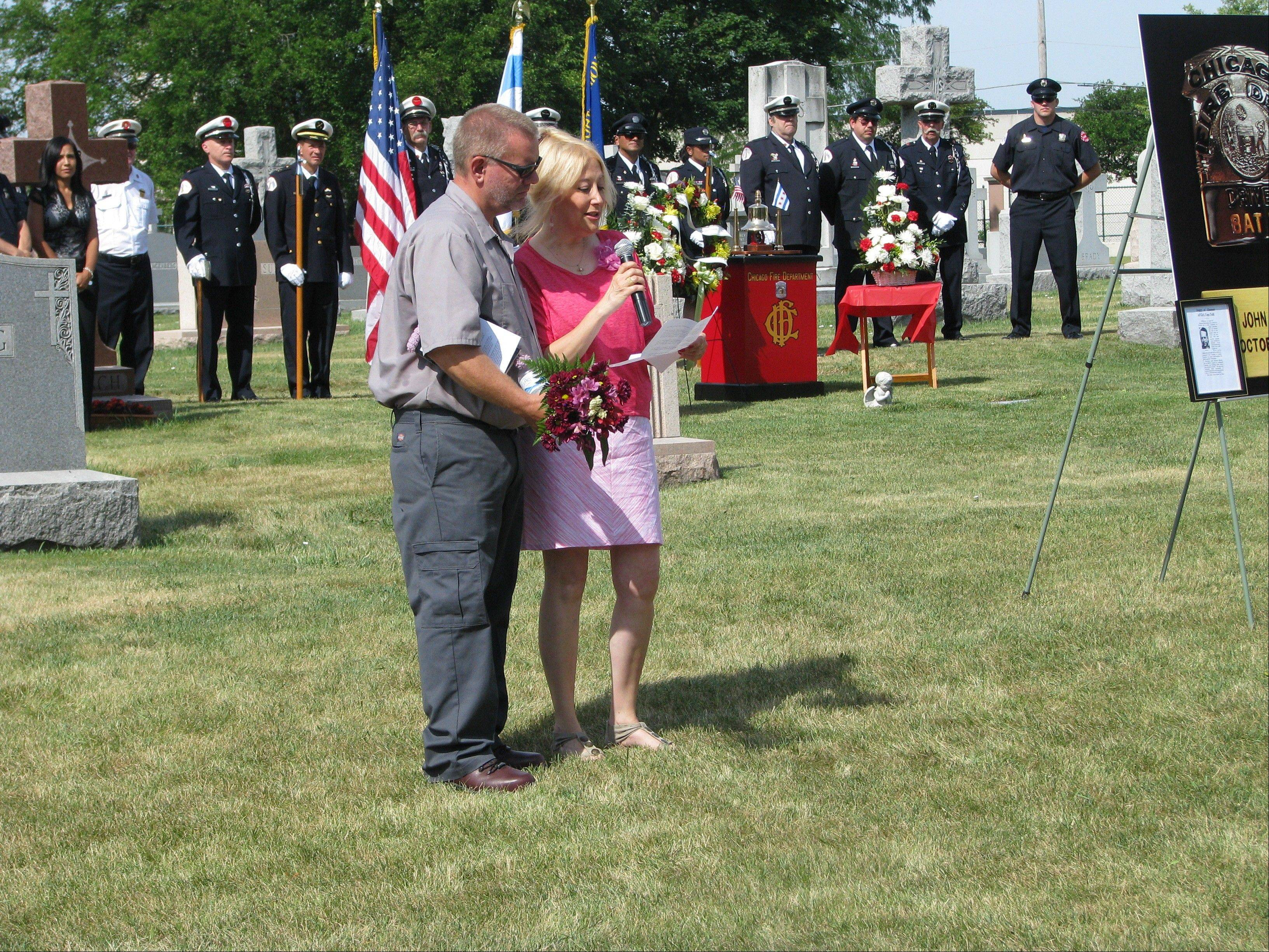 Debbie McCann, whose mother survived the Oct. 25, 1952, Argyle Hotel fire, speaks at the graveside ceremony for John Minich, the firefighter who died after saving her mother, at All Saints Cemetery in Des Plaines. Cemetery employee John Stewart is on the left.