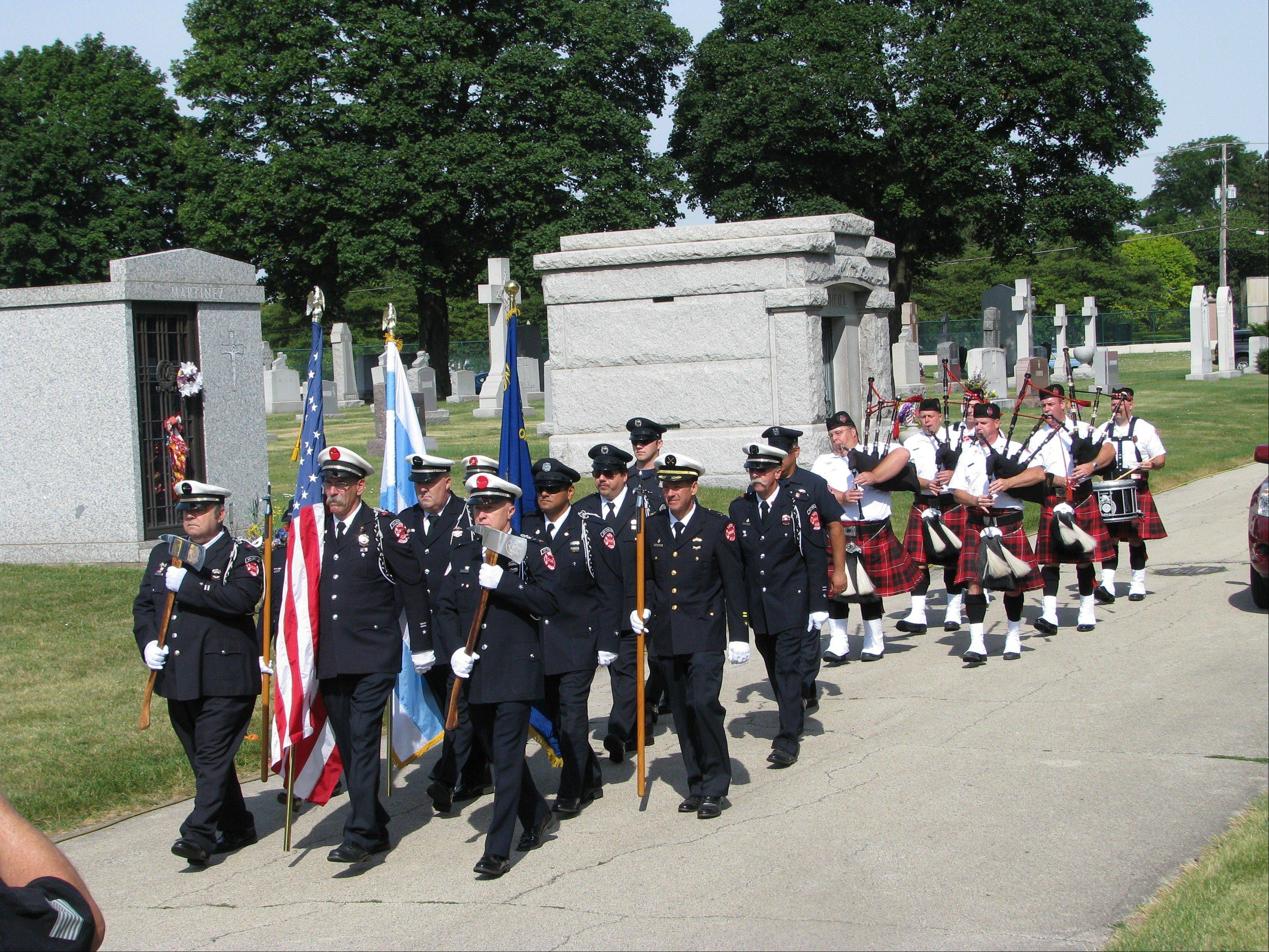 Members of the Chicago Fire Department Pipes and Drums and the Chicago Firefighters Union Local 2 Honor Guard process through All Saints Cemetery in Des Plaines to honor John Minich.