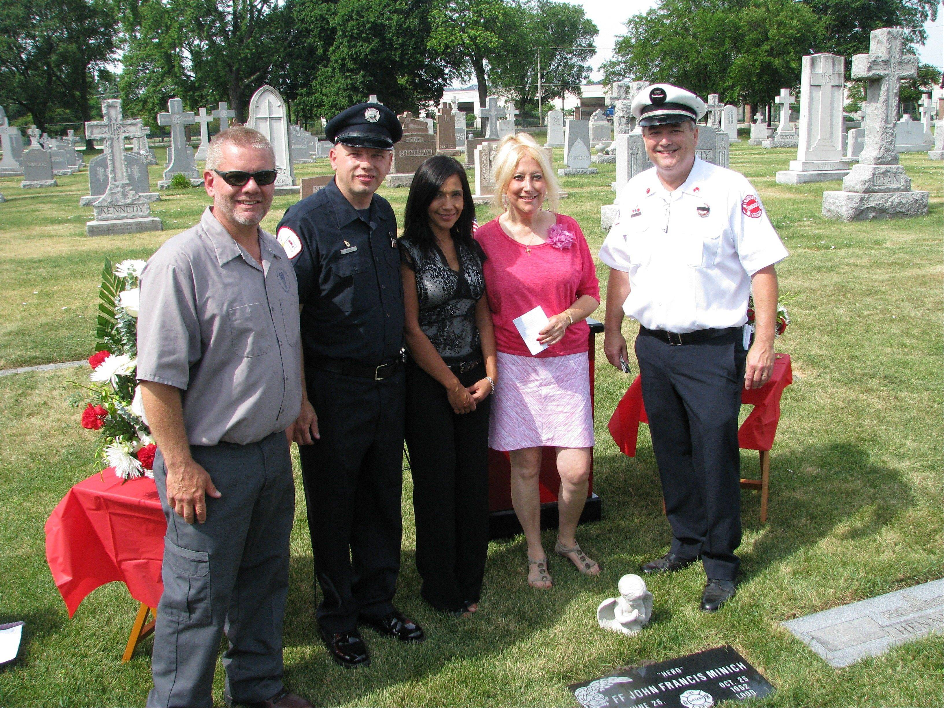 John Stewart, left, an All Saints Cemetery employee; Chicago Firefighter Bob Arens; Tina Diaz, Mount Emblem Cemetery general manager; Debbie McCann, survivor of the 1952 Argyle Hotel fire; and Tom Ryan, CEO Chicago Firefighters Union gather at the new headstone for John Minich.
