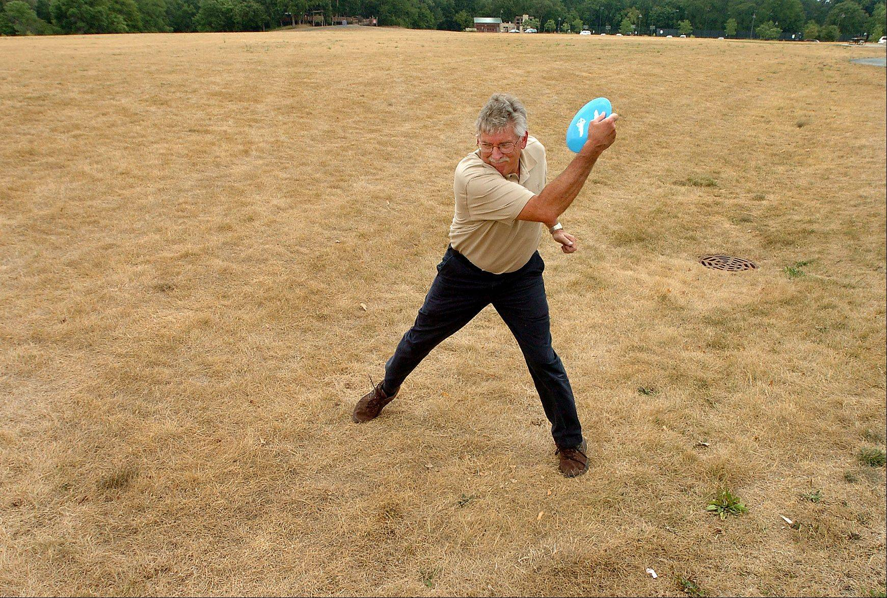 Tom McManus lets fly with a disc while practicing his disc golf skills at a parched Citizens Park in Barrington.