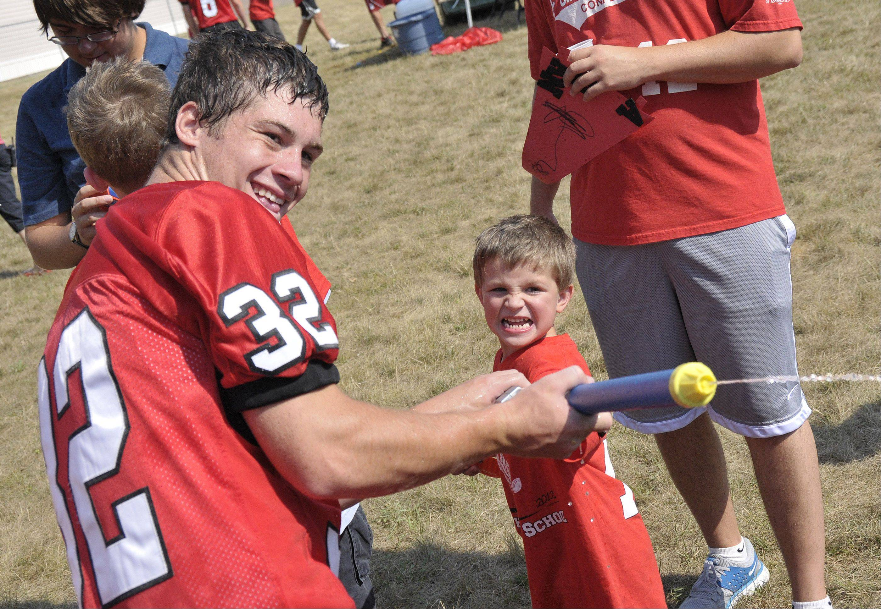 Benet Academy football players helped Southeast School students in Naperville become an 'all star player for a day' Friday morning. They showed the kids some of their football moves and enjoyed other games and activities with them. Benet cornerback Danny Lawler, left, and Southeast student Aidan, (last name withheld) to battle other attendees with water guns.