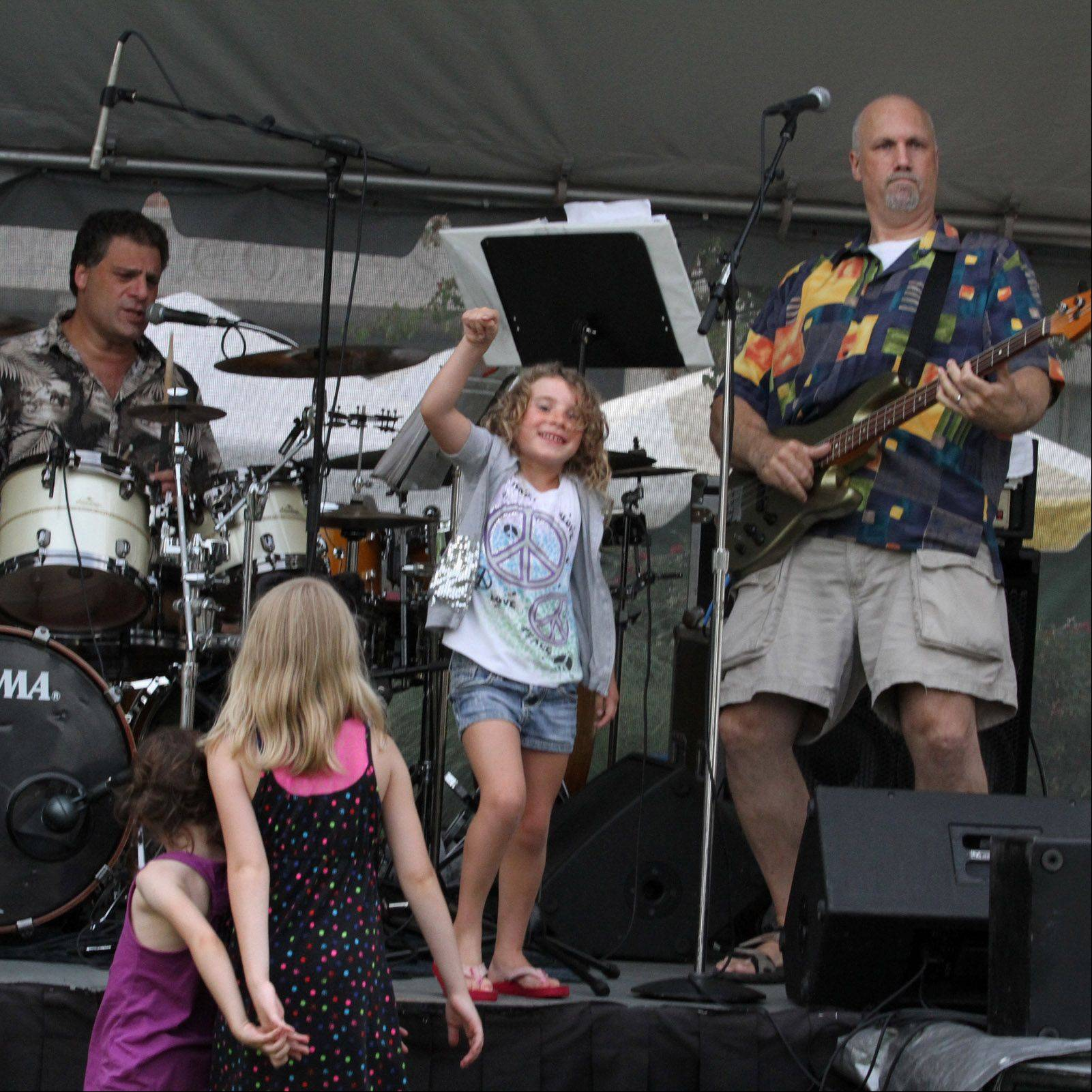 Sarah Horwitz, 5, of Lincolnshire dances onstage to rock music by Jukebox Band with Steve Tschaikowsky of Mettawa playing guitar, right, at 11th Annual Taste of Lincolnshire at Village Green on Friday.