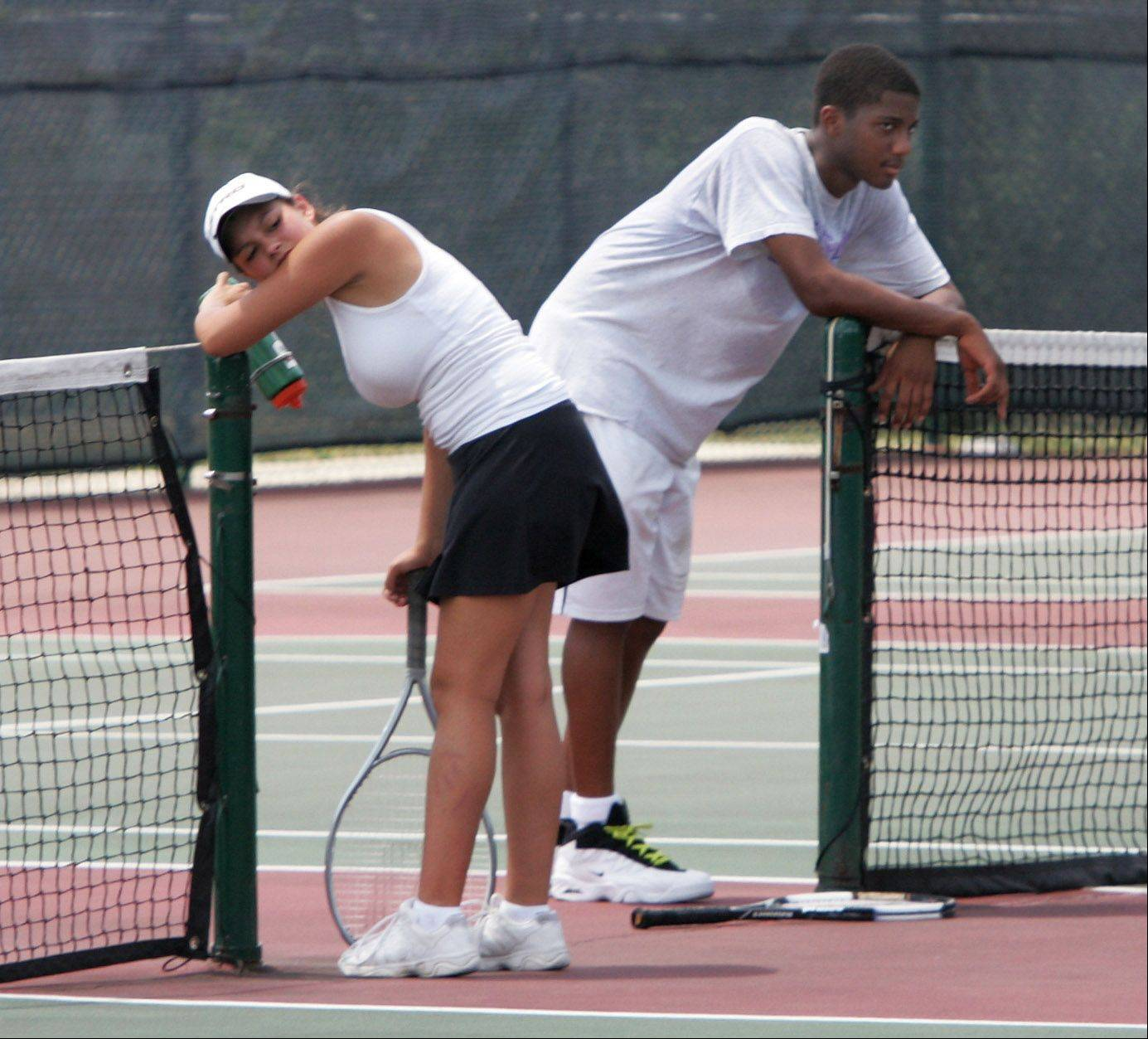 Nicole Garcia, 17, left, and Aaron Jackson, 18, are exhausted after coaching tennis at Grayslake Central High School's summer tennis camp Tuesday. The temperatures soared toward 100 degrees for another day adding to the extremely hot summer.