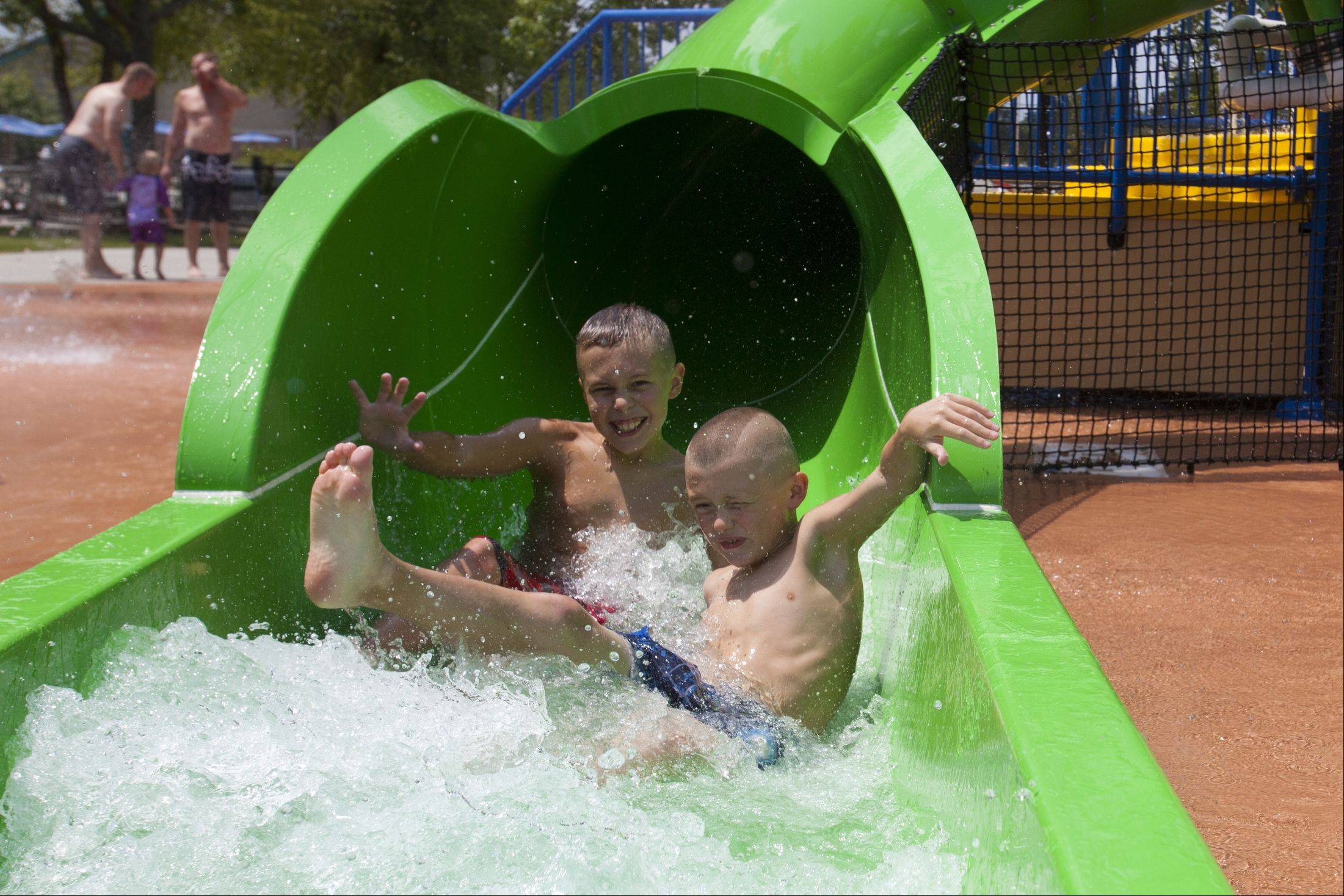 Evan James Spresser, 10, and his brother Cole Michael, 8, of Bartlett splash down a slide at the Bartlett Aquatic Center trying to stay cool in over 90 degree heat.