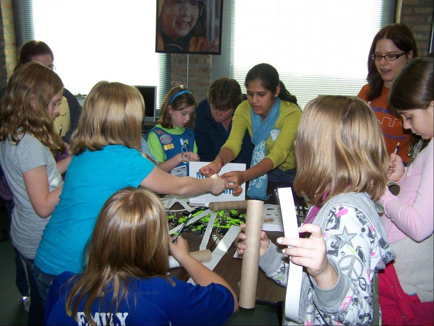 Katrin Hoeper, senior security research engineer, and Pooja Gautham, senior software engineer, teach Girl Scouts about careers in engineering at a Science Fair held at Journey World, Girl Scouts of Greater Chicago and Northwest Indiana�s experiential learning center.