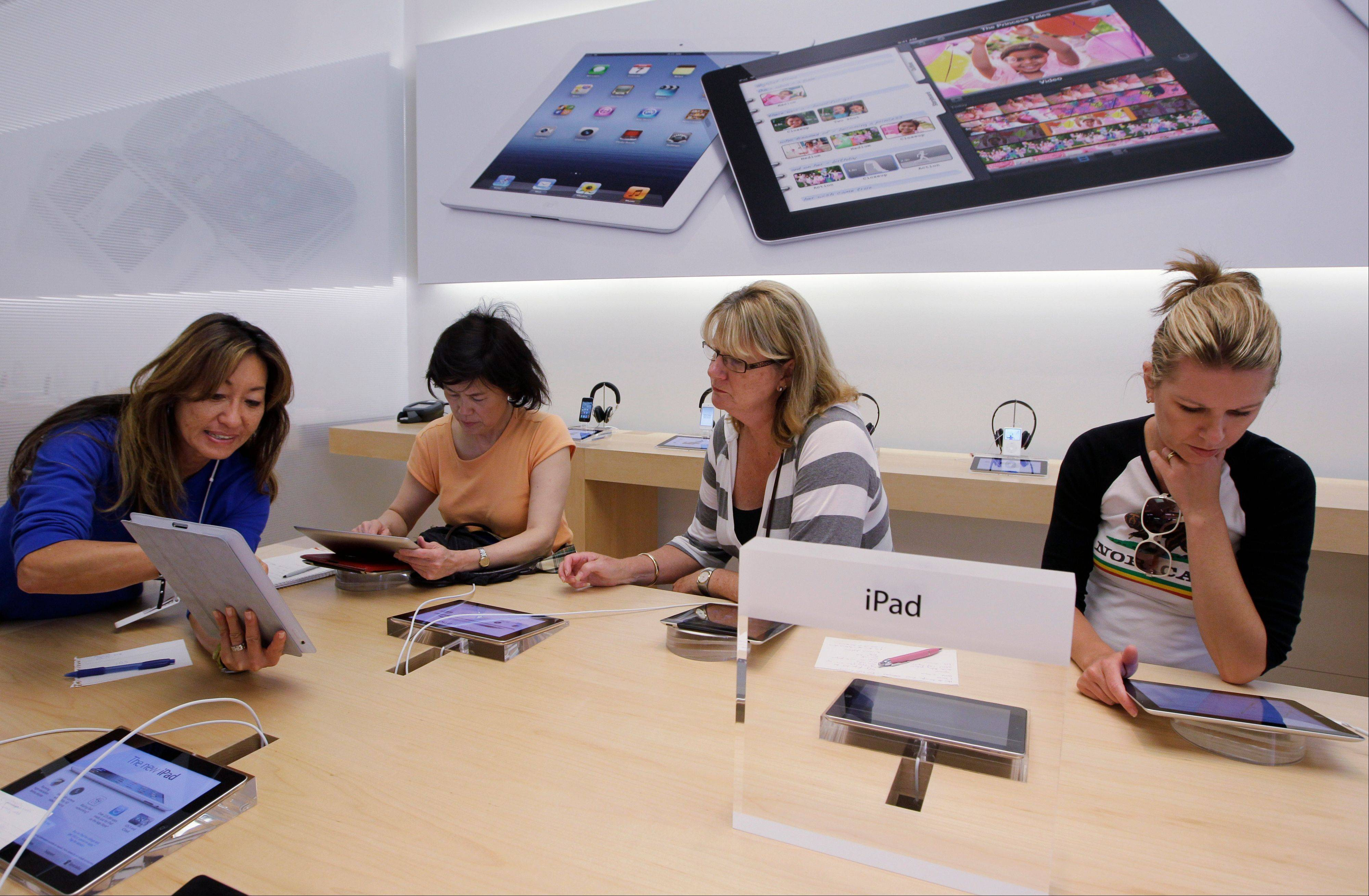 An Apple worker, left, gives a tutorial on Apple iPad to customers at an Apple store in Palo Alto, Calif.