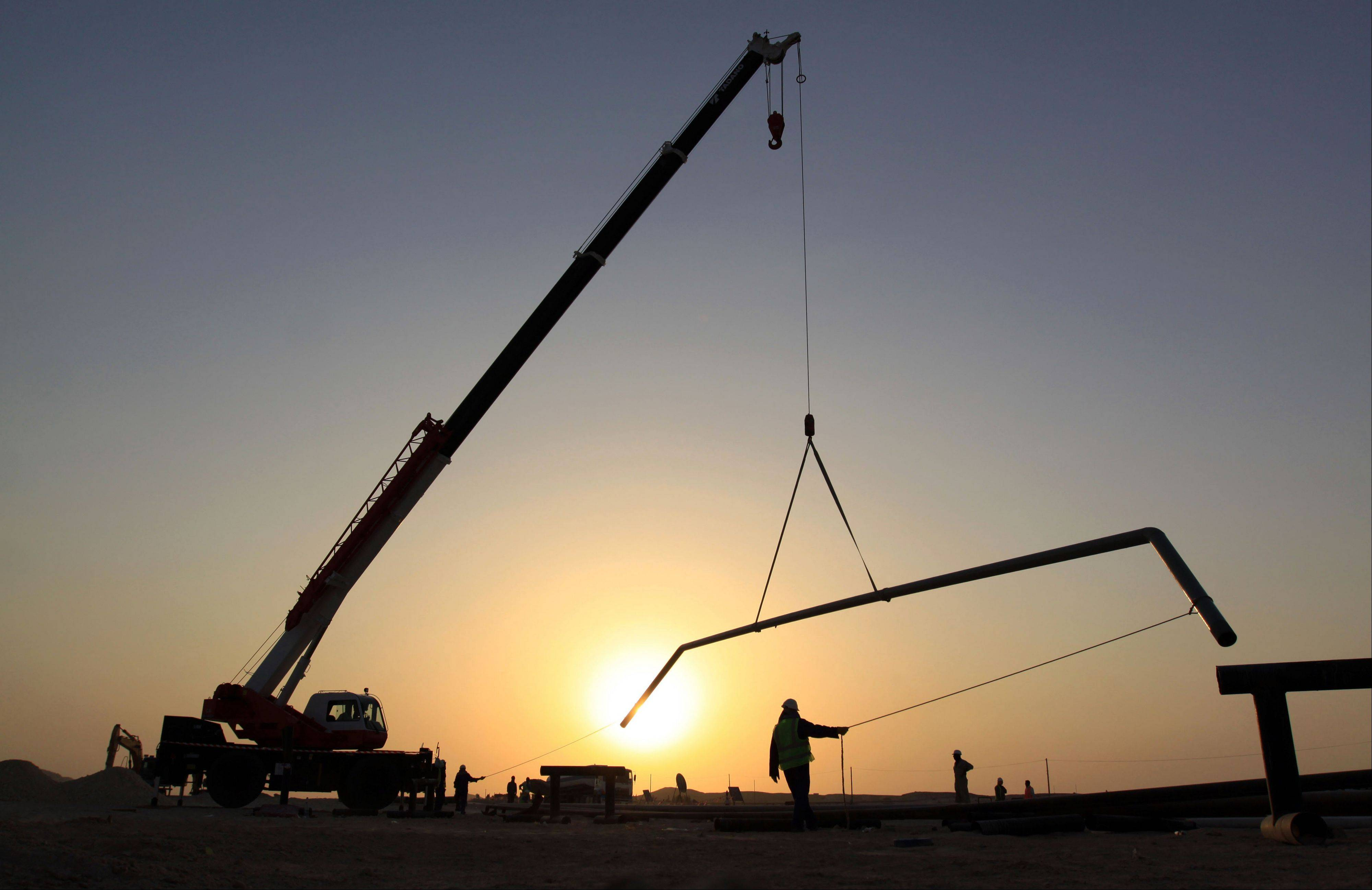 Oil workers are seen fixing pipes at sunset in the desert oil fields of Sakhir, Bahrain.