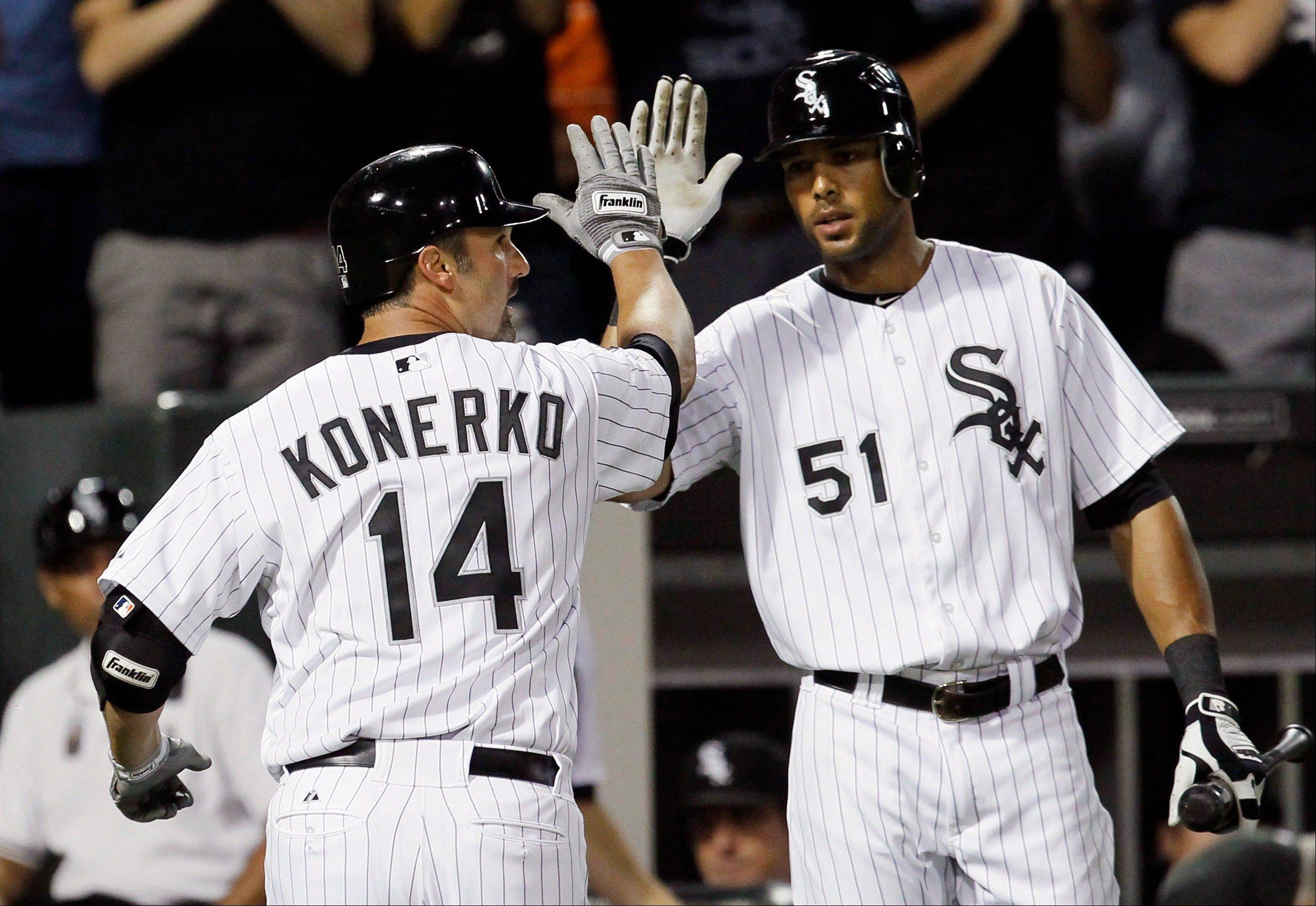 White Sox first baseman Paul Konerko looks back at left field as he celebrates his home run off Minnesota Twins starting pitcher Cole De Vries with Alex Rios Tuesday during the fifth inning.