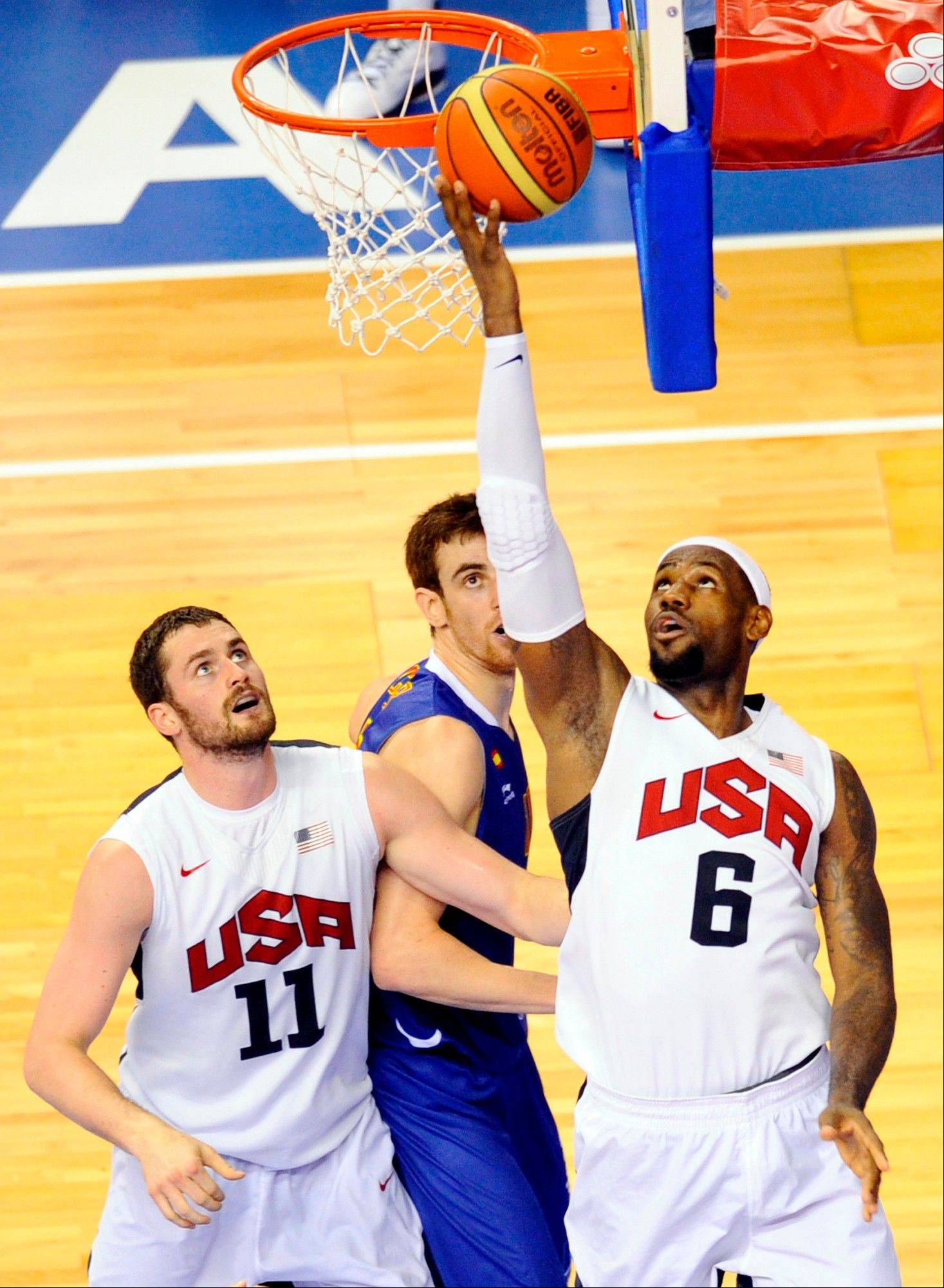 LeBron James, right, dives for the ball against Victor Claver, center, of Spain Men�s Senior National Team Tuesday during an exhibition match in Barcelona, Spain.