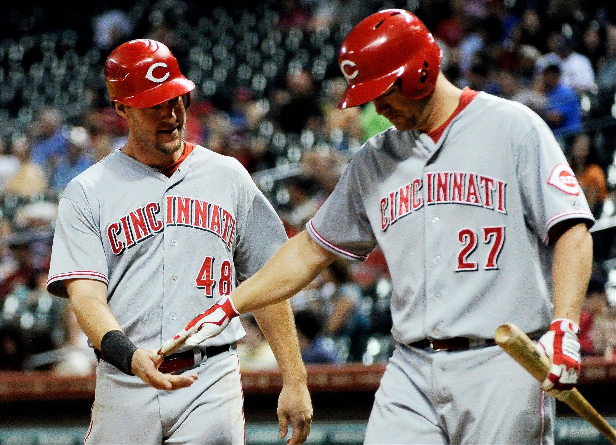 The Reds� Scott Rolen (27) welcomes home Ryan Ludwick after he scored on a double by Todd Frazier in the eighth inning Monday in Houston.