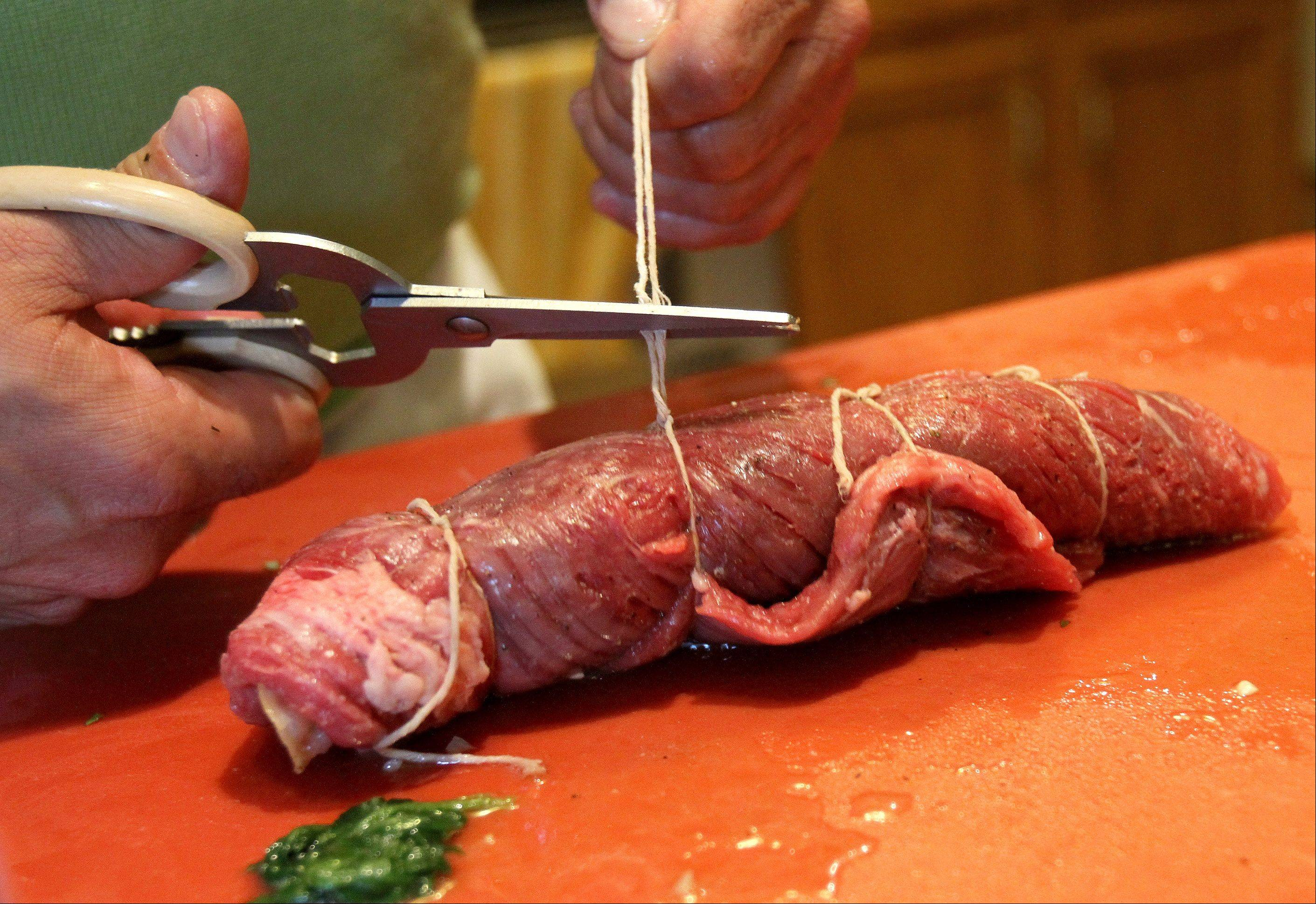 Tony Barone rolls spinach and provolone cheese into his braciole.