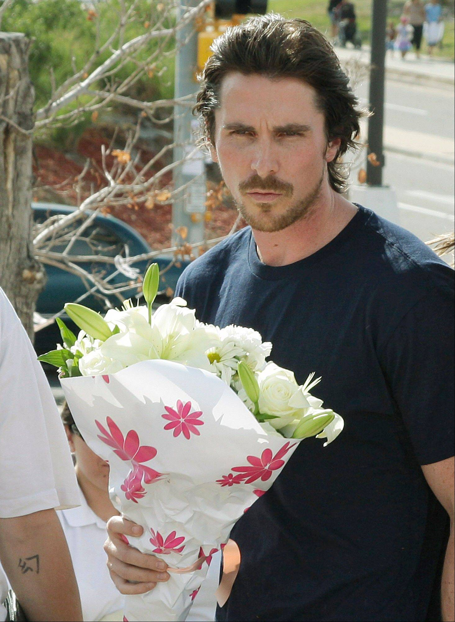 "Actor Christian Bale carries flowers Tuesday as he visits a memorial to the victims of Friday's mass shooting n Aurora, Colo. Twelve people were killed when a gunman opened fire during a late-night showing of the movie ""The Dark Knight Rises"", which stars Bale as Batman."