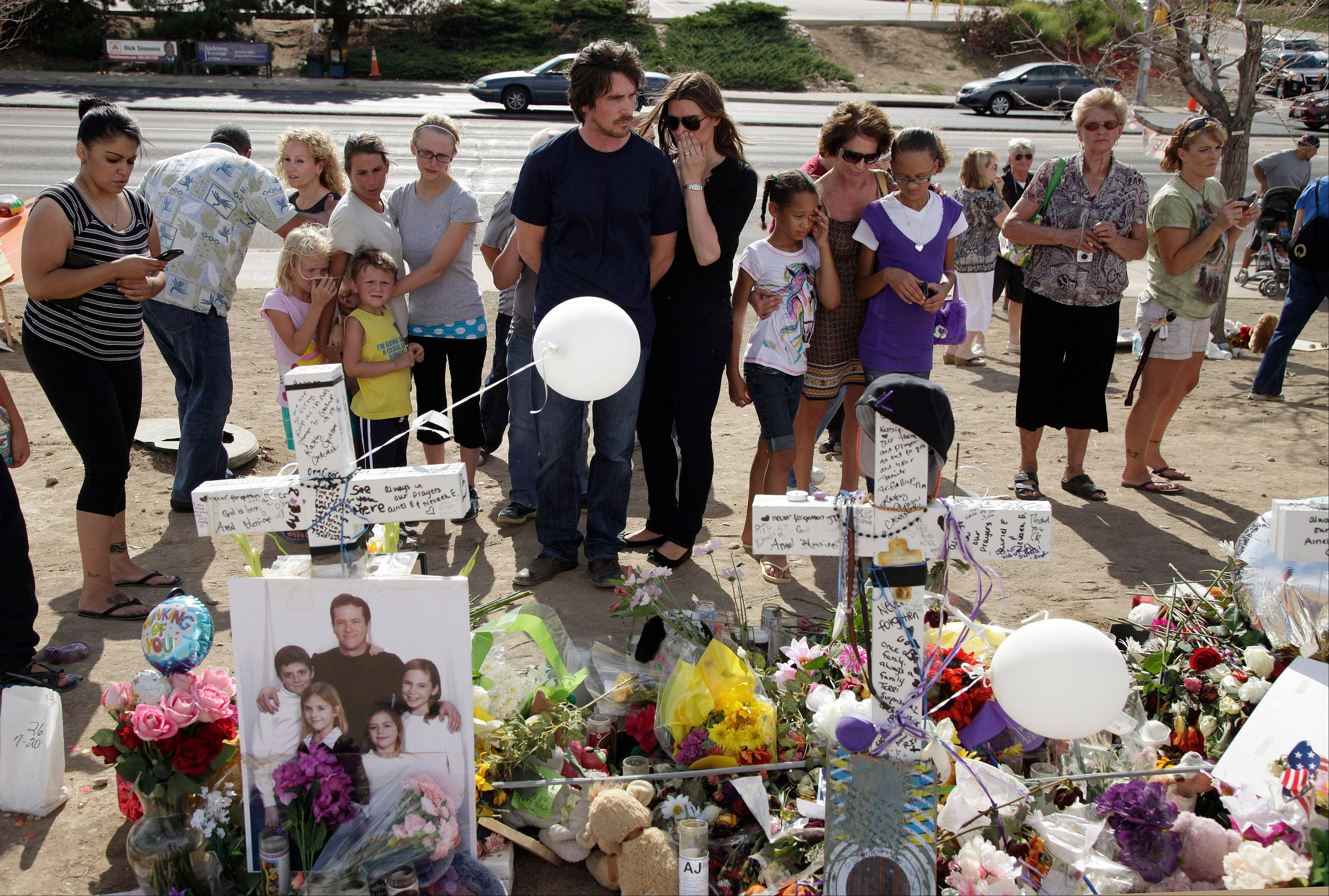 "Actor Christian Bale, center, and his wife Sibi Blazic visit a memorial to the victims of Friday's mass shooting in Aurora, Colo. Twelve people were killed when a gunman opened fire during a late-night showing of the movie ""The Dark Knight Rises,"" which stars Bale as Batman."