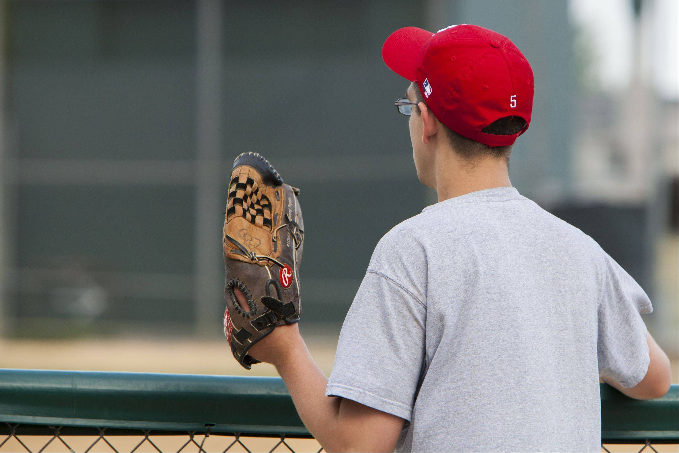 "Michael Lavoie, a player from the Bartlett Little League Challenger Division, stands at the outfield fence with his glove before telling the coaches to ""cover the field before the rain comes."" That afternoon's games were cancelled due to the heat."