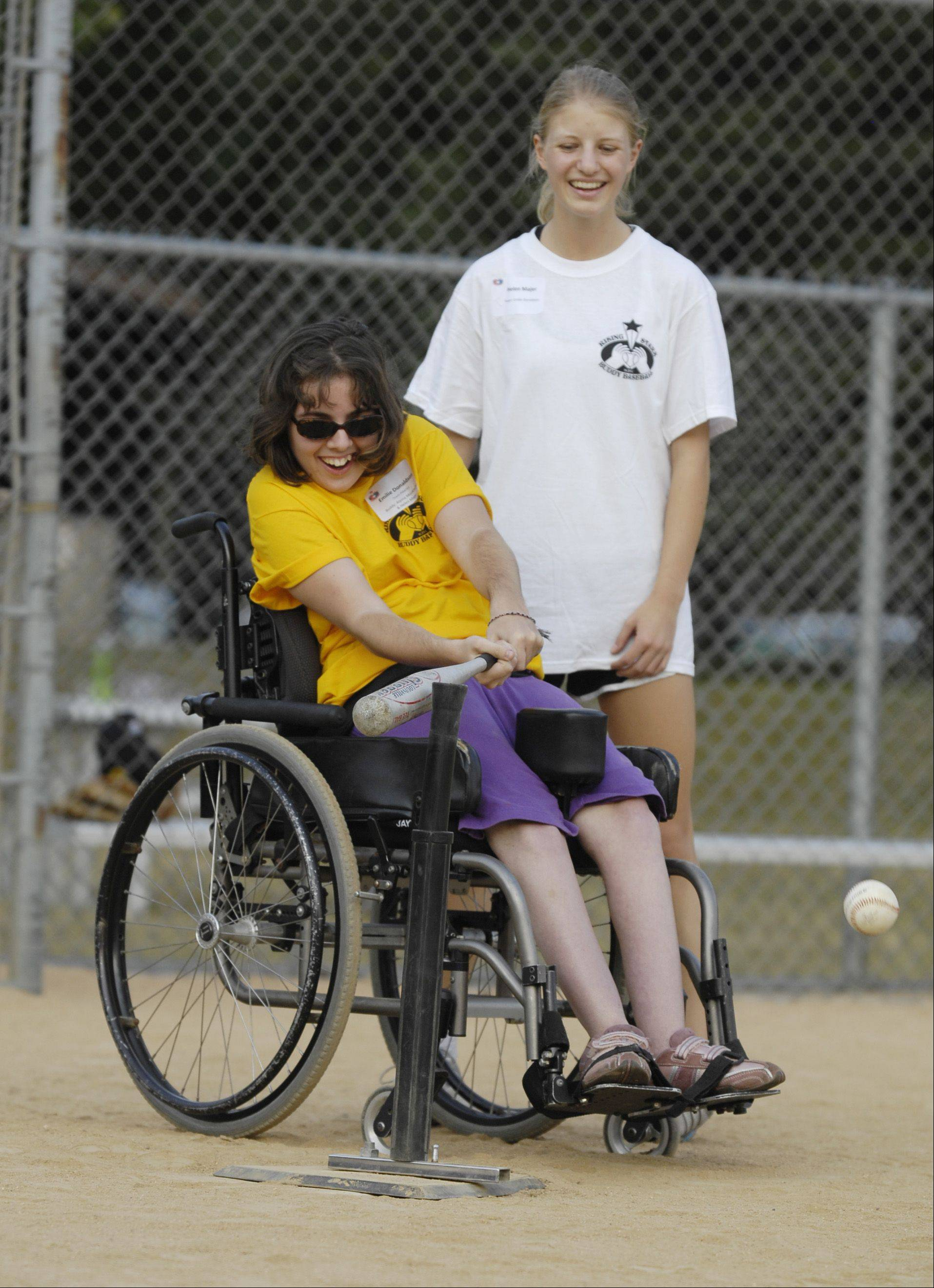 "Player Emilie Donaldson and her ""buddy"" Helen Majer take a turn batting during the first buddy baseball game of the season at Briar Patch Park in Wheaton. The league is sponsored by the Wheaton Junior Women's Club."