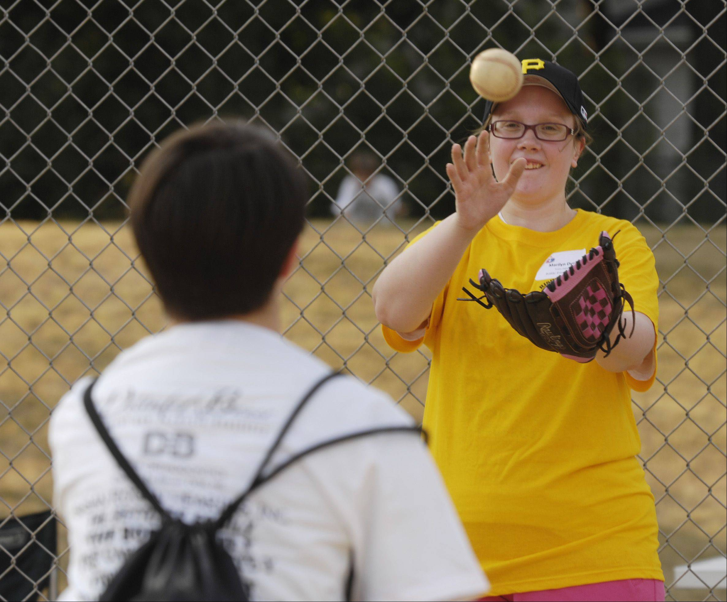 "Player Marilyn Dyrda, right, and her ""buddy"" Erin Markovich warm up before the first buddy baseball game of the season at Briar Patch Park in Wheaton. The league is sponsored by the Wheaton Junior Women's Club."