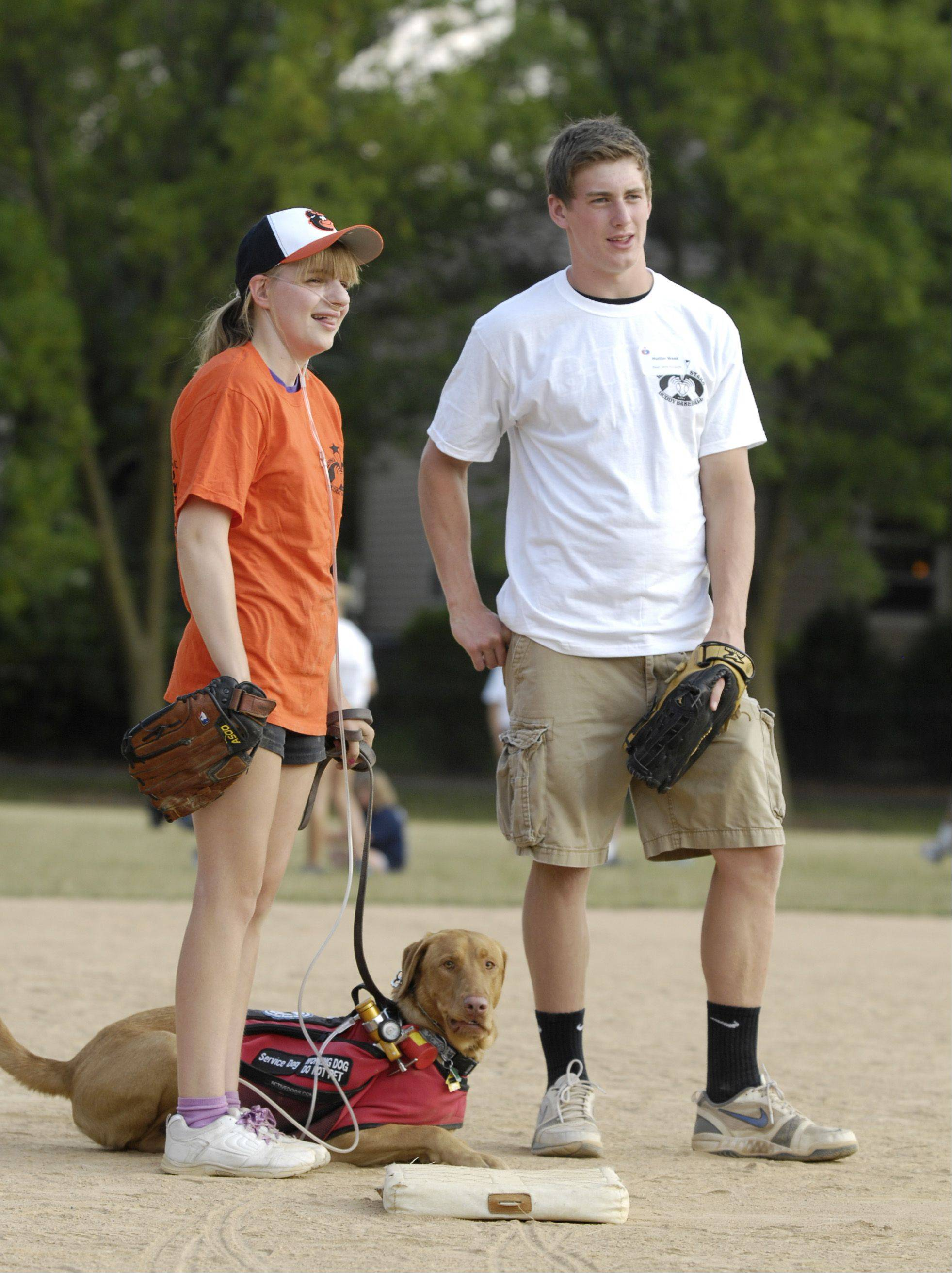 "Player Jenny Youngwith, her service dog Bode and her ""buddy"" Hunter Week play third base during the first buddy baseball game of the season at Briar Patch Park in Wheaton. The league is sponsored by the Wheaton Junior Women's Club."