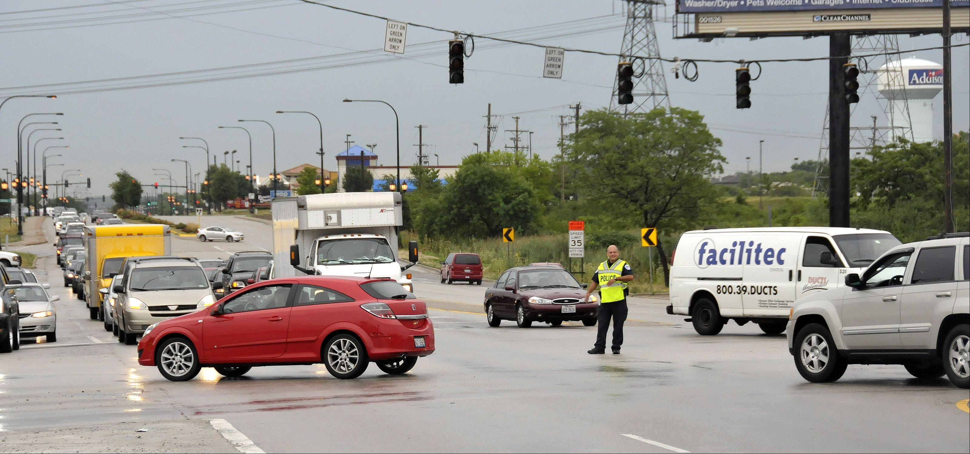 With traffic backing up and the power out, police officers direct traffic at Lake Street and Route 53 in Addison following a strong storm that hit the area Tuesday morning.