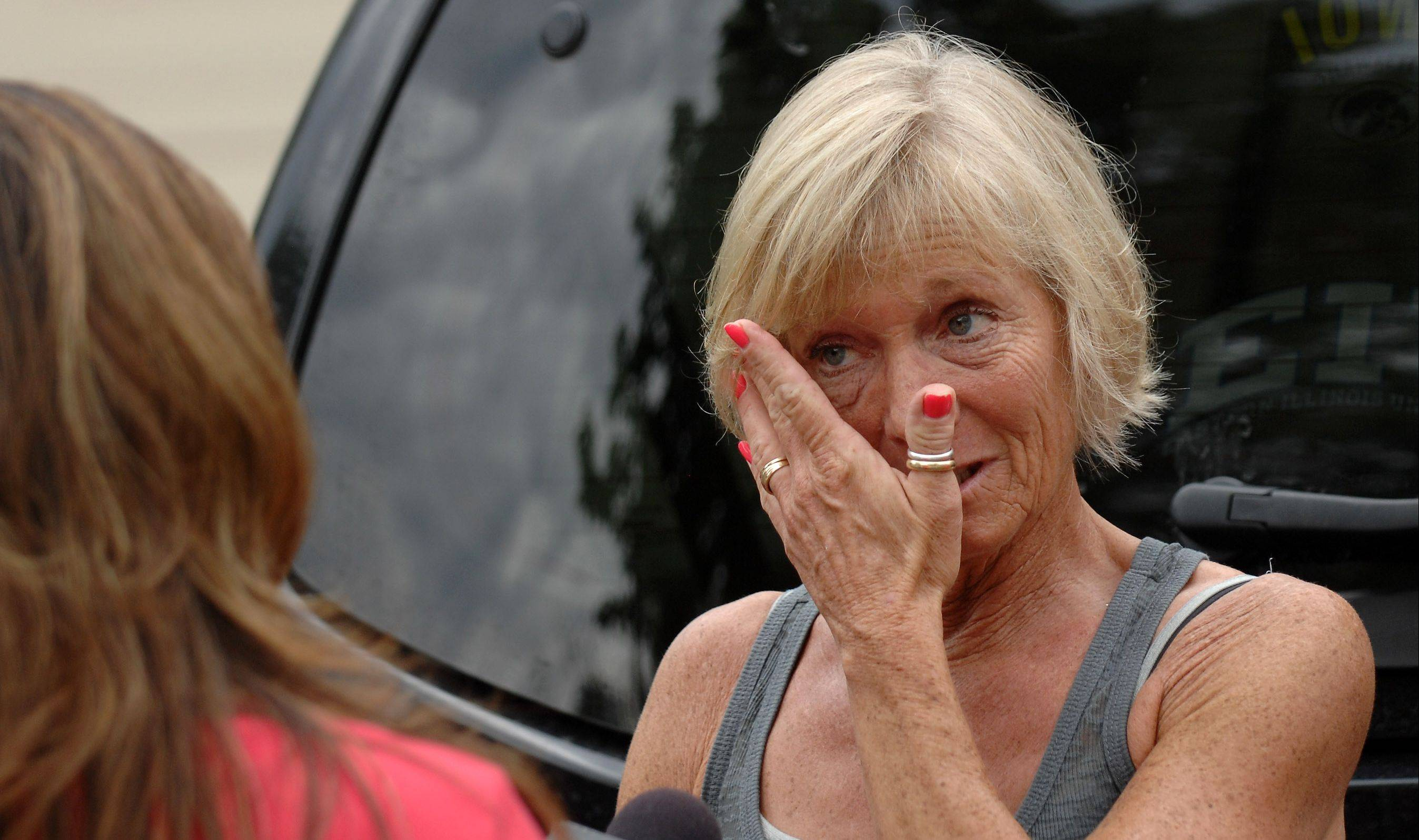 Debbie Vojtsek wipes away a tear while speaking to the media outside the home of her niece Julia Vojtsek in Algonquin. Julia said her boyfriend, John Larimer of Crystal Lake, saved her life by shielding her from the bullets that claimed him and 11 others in the movie theater shooting in Colorado Friday. Debbie Vojtsek talked about his bravery and how appreciative her family is for the actions that saved the life of her niece.