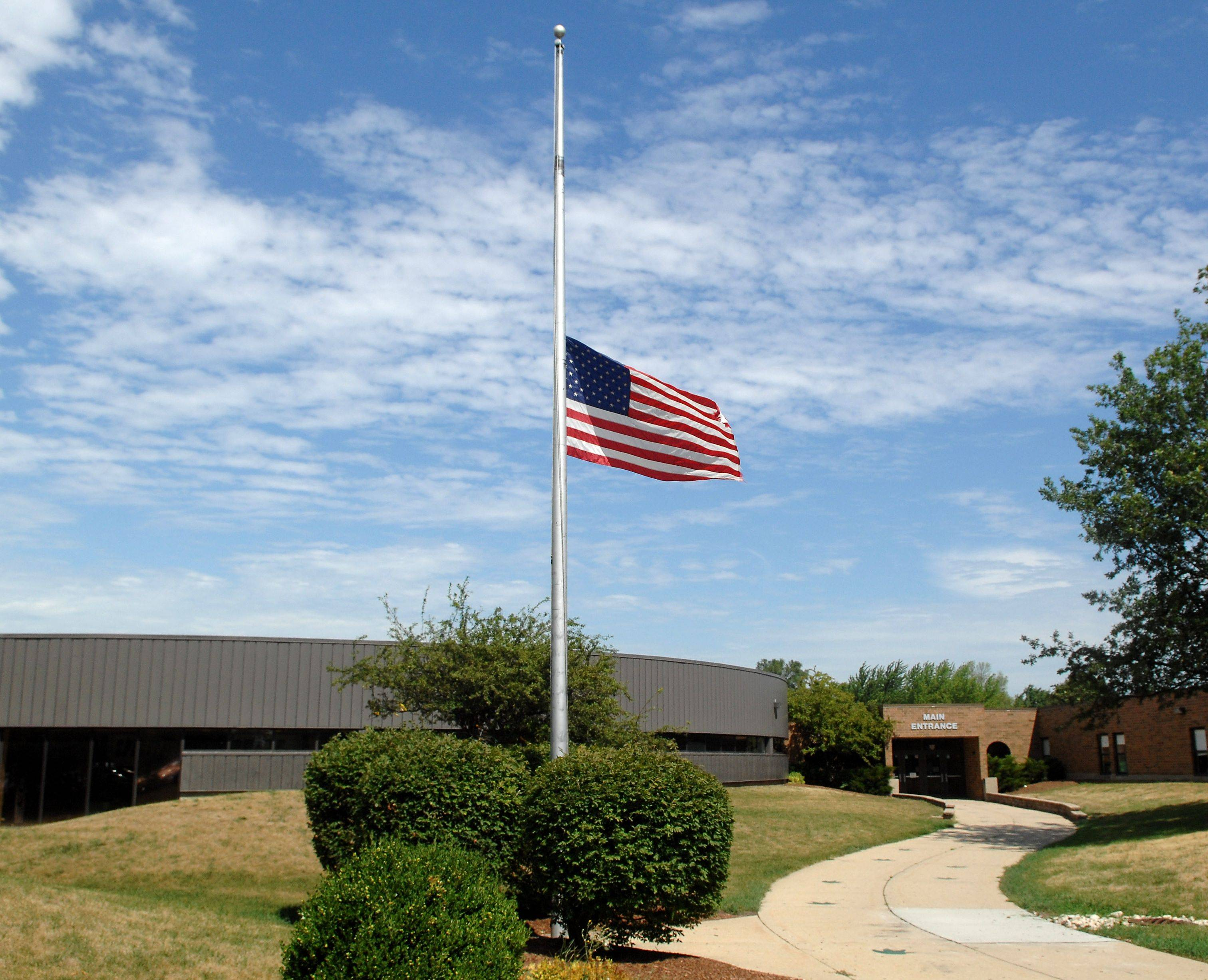 The flag was at half staff at Crystal Lake South High School Monday in honor of alumnus John Larimer, who was killed along with 11 others in the theater shooting in Colorado.