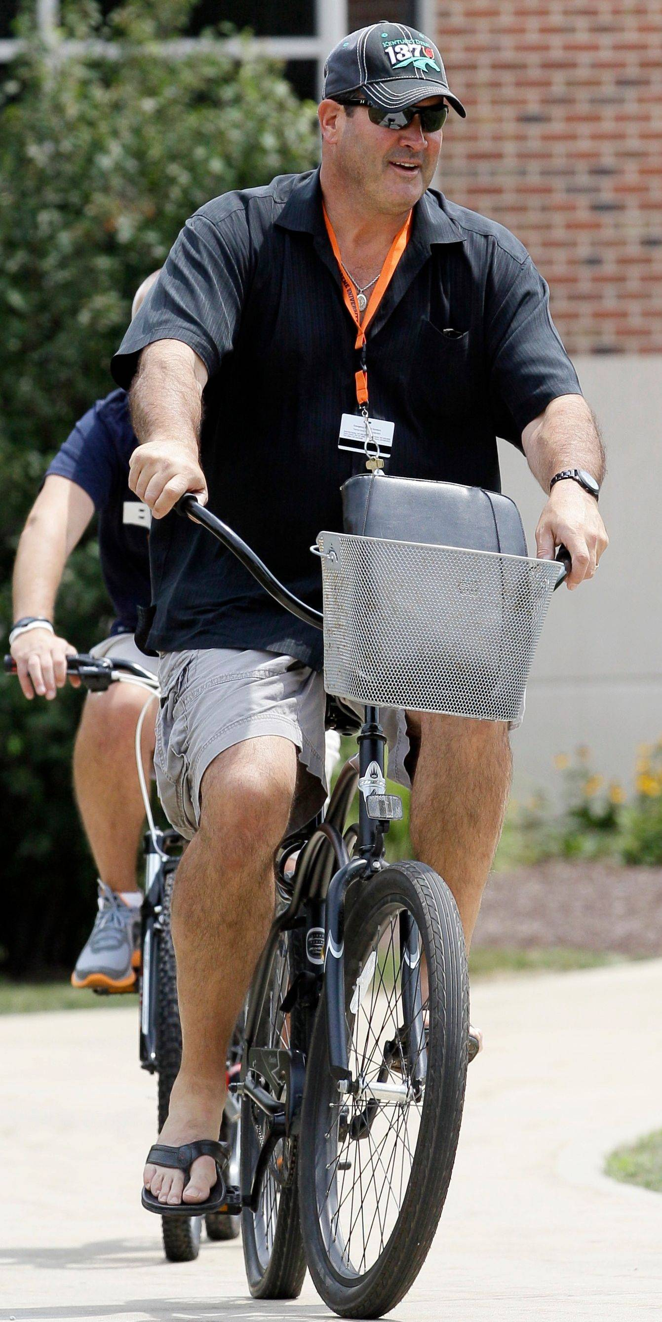 Offensive coordinator Mike Tice rides a bicycle at Olivet Nazarene University in Bourbonnais on Tuesday. Training camp starts in earnest Thursday.