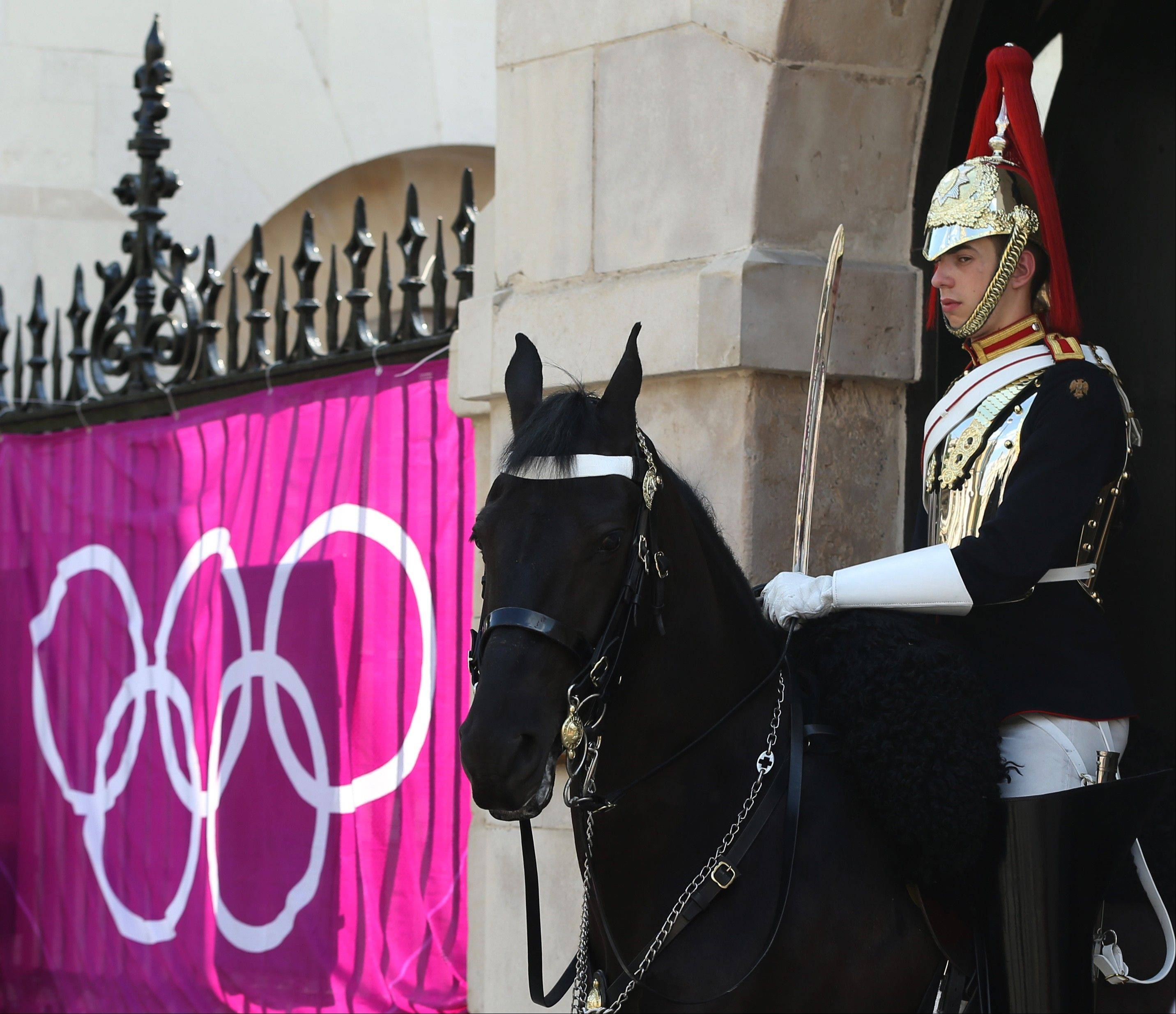 A member of the Horse Guards Parade stands watch outside the Admiralty House at the 2012 Summer Olympics on Wednesday in London. NBC said it has already sold $1 billion in ads for the Games.