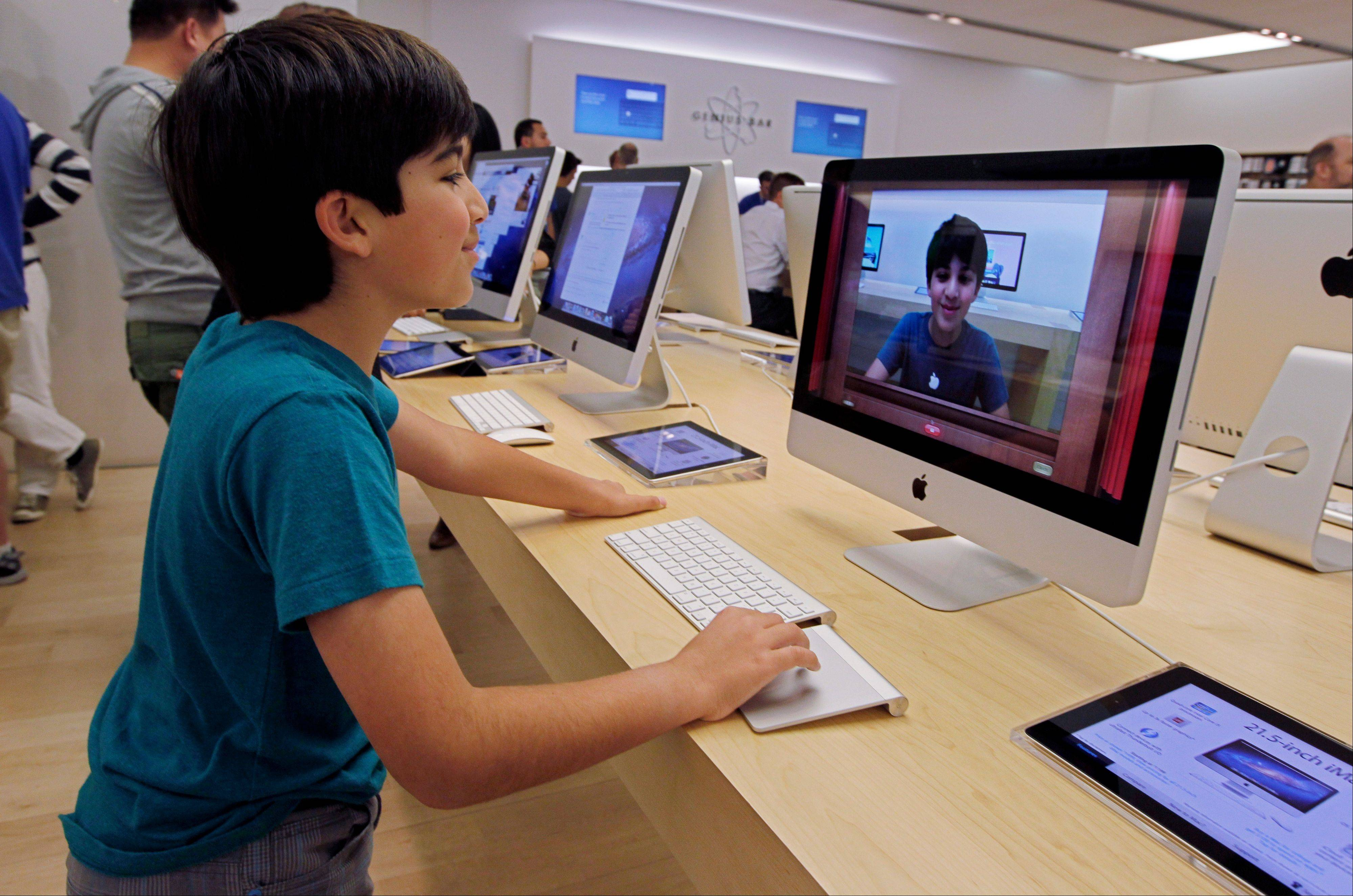 An Apple customer Shayan Hooshmand, 11, uses PhotoBooth on a 21.5-inch iMac at an Apple store in Palo Alto, Calif.