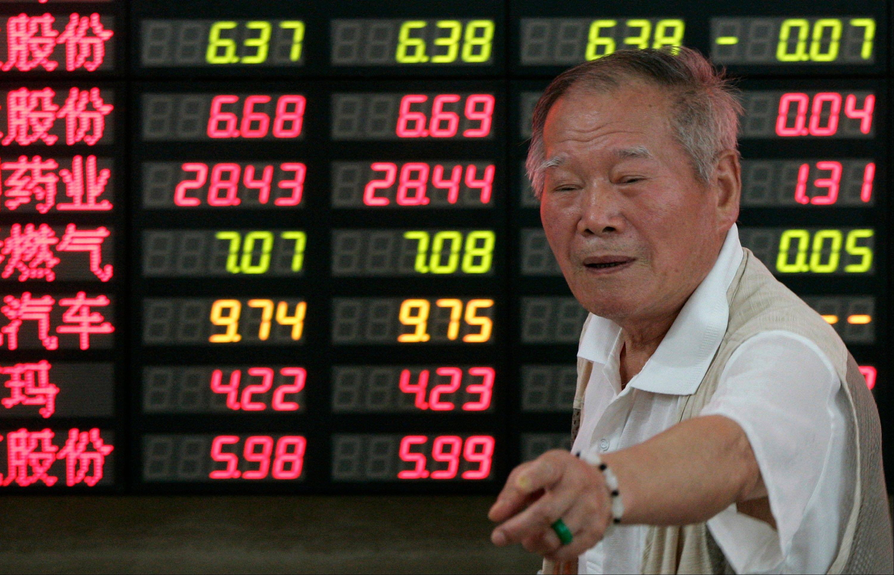 An investor gestures in front of the stock price monitor at a private securities company Tuesday July 24, 2012 in Shanghai, China.