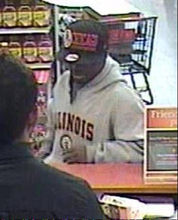 Courtesy of the FBI Surveillance photos show a suspect robbing a TCF Bank branch inside a Bartlett Jewel-Osco on June 6. The suspect is wanted in connection to a Monday morning robbery of a Elmhurst bank.