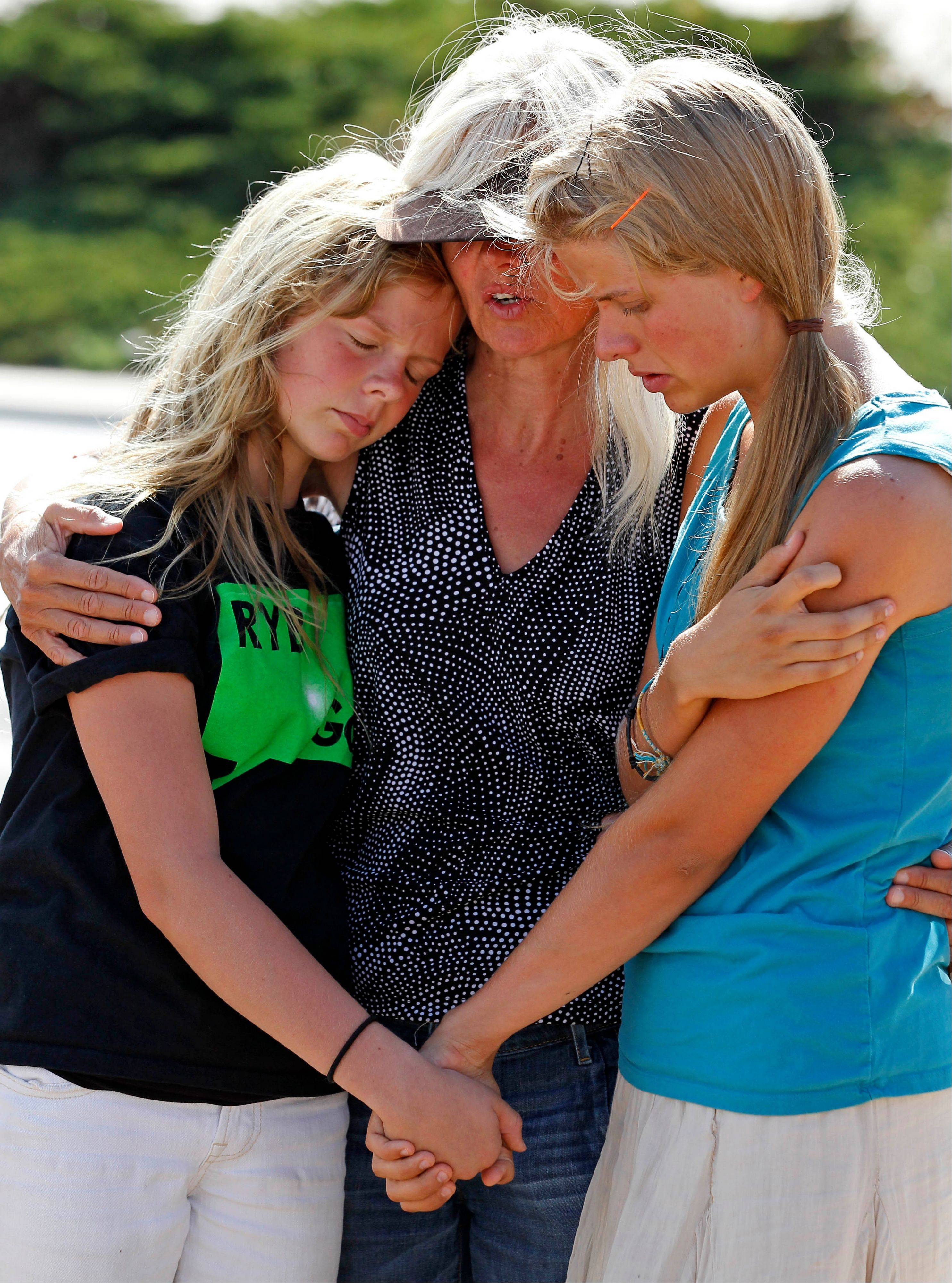 Shadia Sikkema, 12, left, her mother, Diane Sikkema, and sister, Spenser Sikkema, 19, visit the memorial across from the movie theater Wednesday in Aurora, Colo.