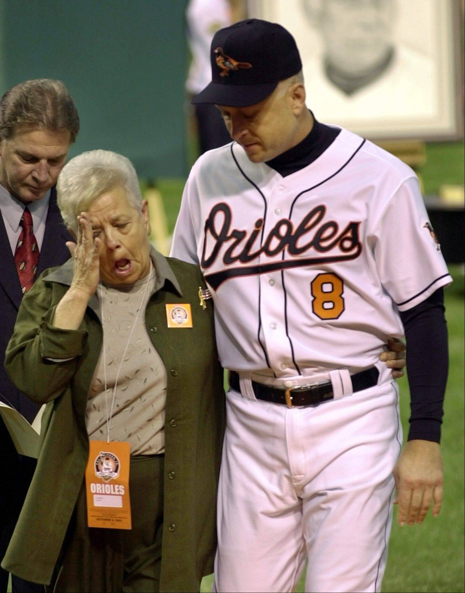 FILE - This Oct. 6, 2001, file photo shows Cal Ripken escorting his mother, Vi, from the field, after throwing out the ceremonial first pitch before Cal's final game at Oriole Park in Baltimore.