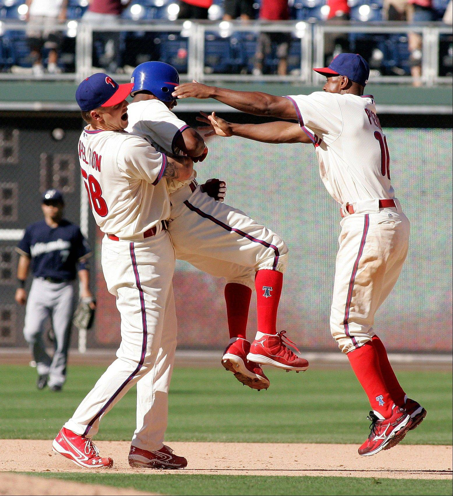 Philadelphia Phillies pitcher Jonathan Papelbon, left, lifts teammate Jimmy Rollins up as Juan Pierre, right, joins in to celebrate Rollins� game-winning RBI Wednesday during the 10th inning in Philadelphia. The Phillies beat the Brewers 7-6.