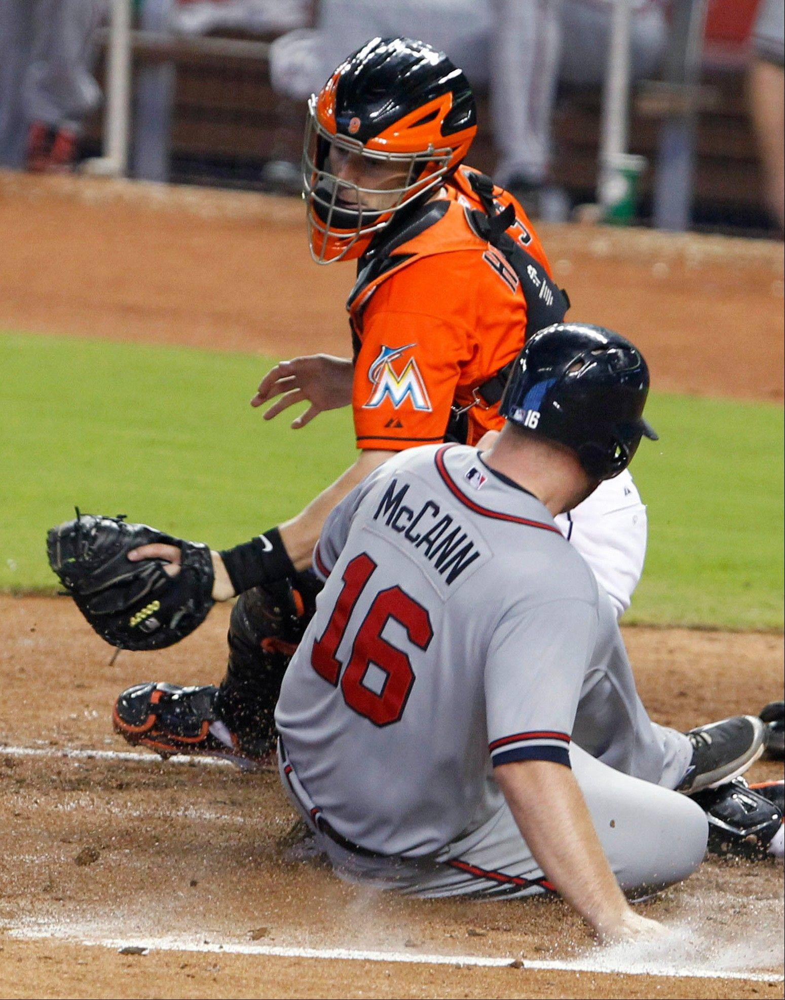 Atlanta Braves catcher Brian McCann scores as Miami Marlins catcher Brett Hayes attempts the tag Wednesday during the sixth inning in Miami. The Braves defeated the Marlins 7-1.