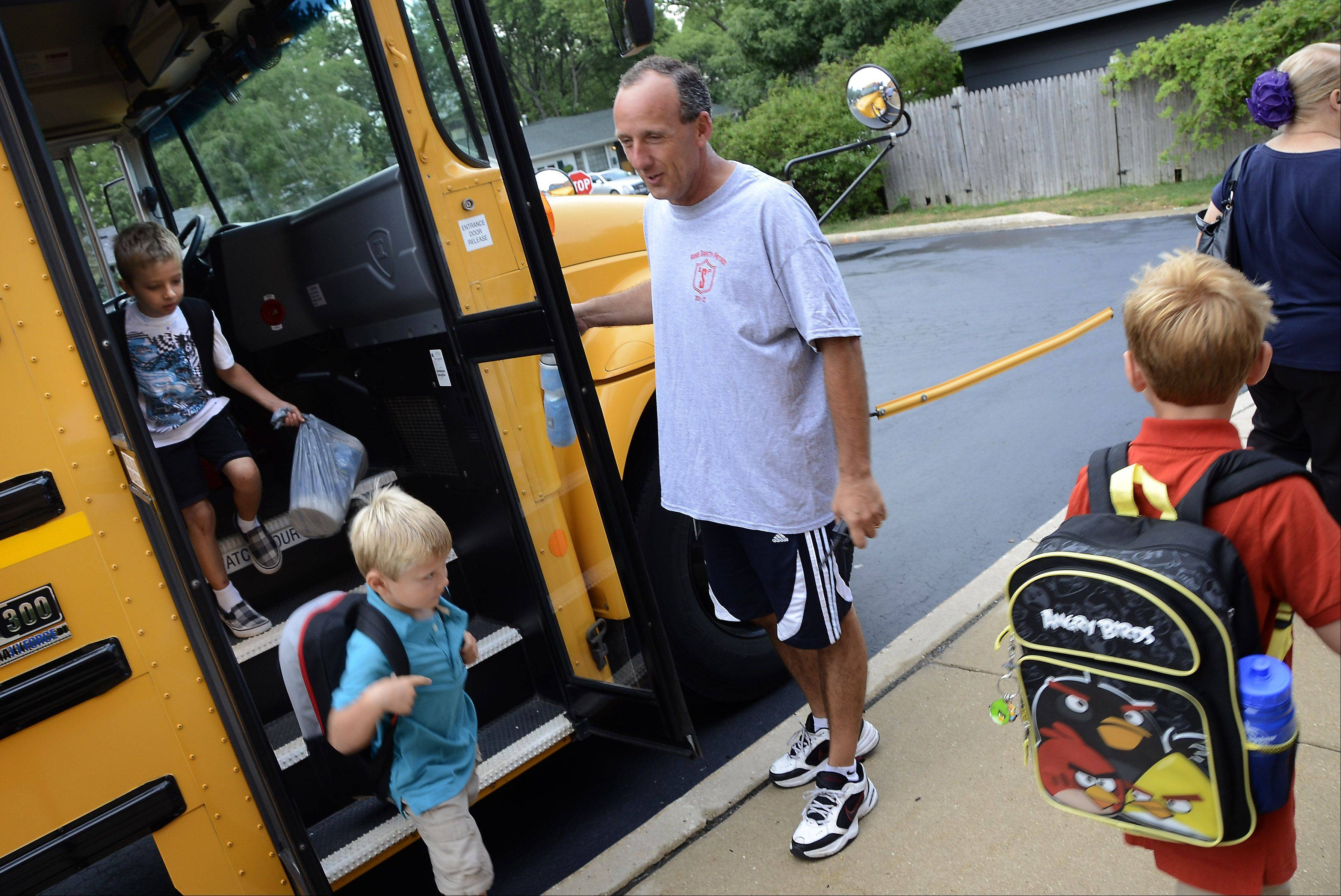 Physical education teacher Will Hogan greets students as they return Wednesday morning.