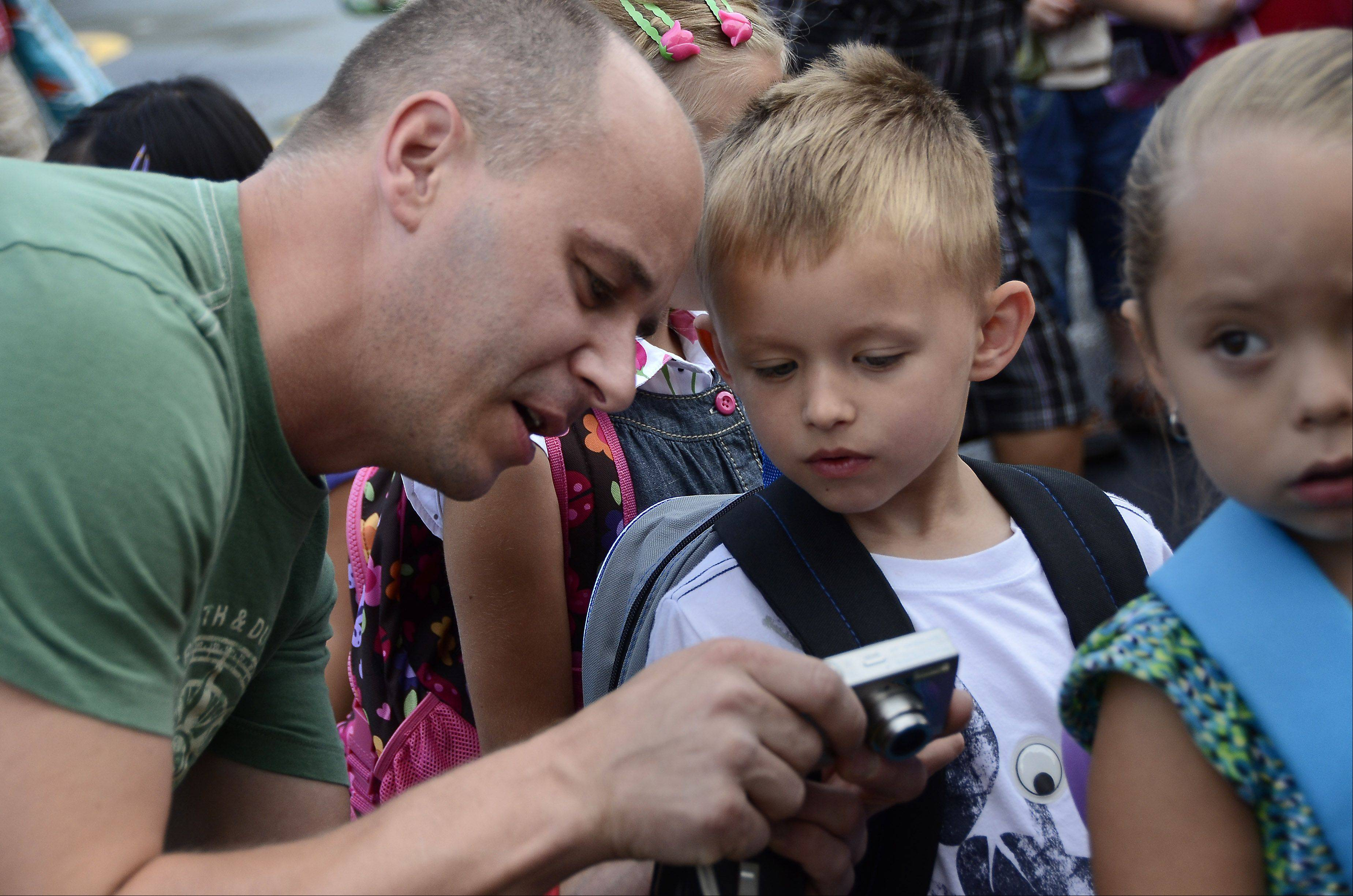 Giak Wojtek shows his son, Maximilian, 5, the picture he took of him as students start classes Wednesday.