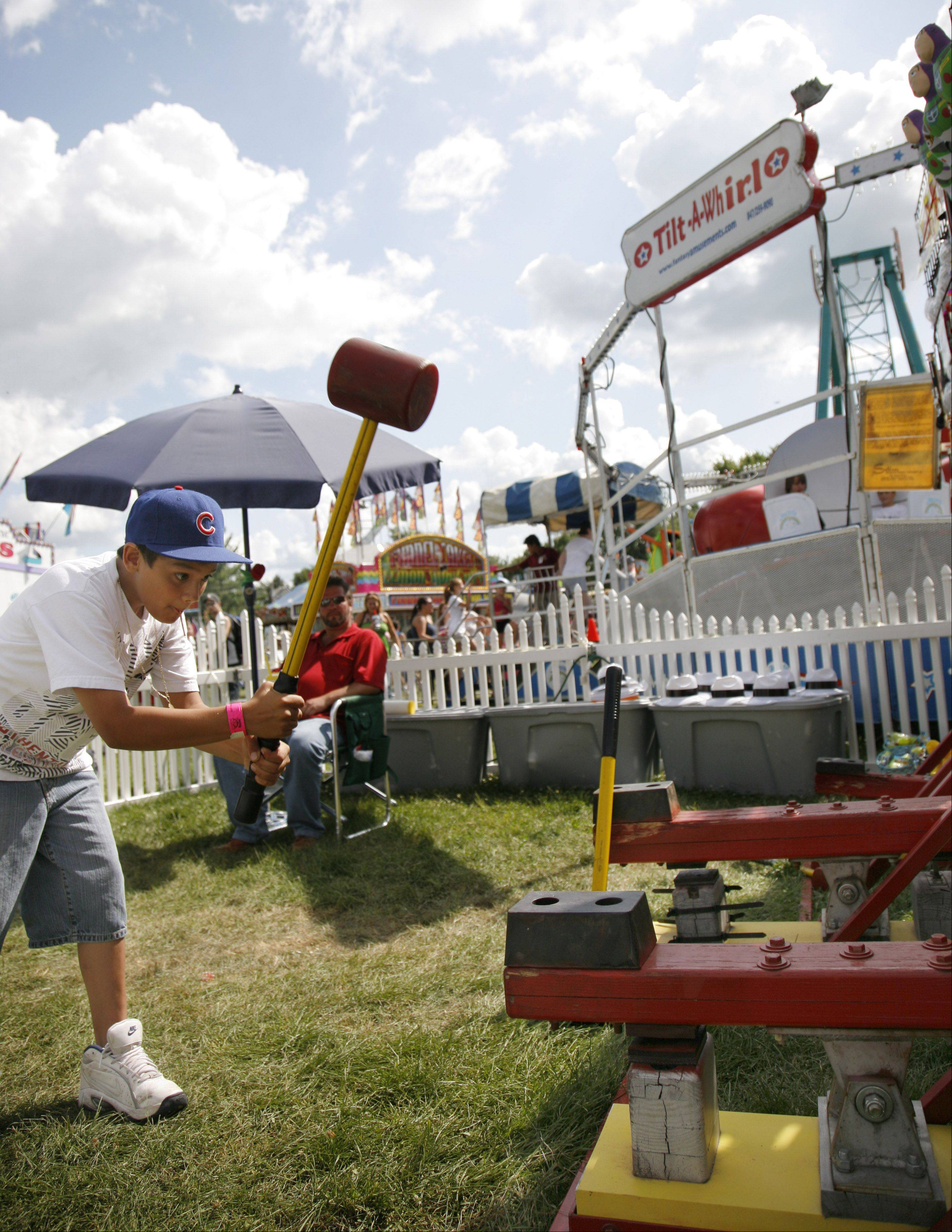 Ivan Cadema, 11, of Plano takes a whack at a carnival game during a previous Sugar Grove Corn Boil festival.