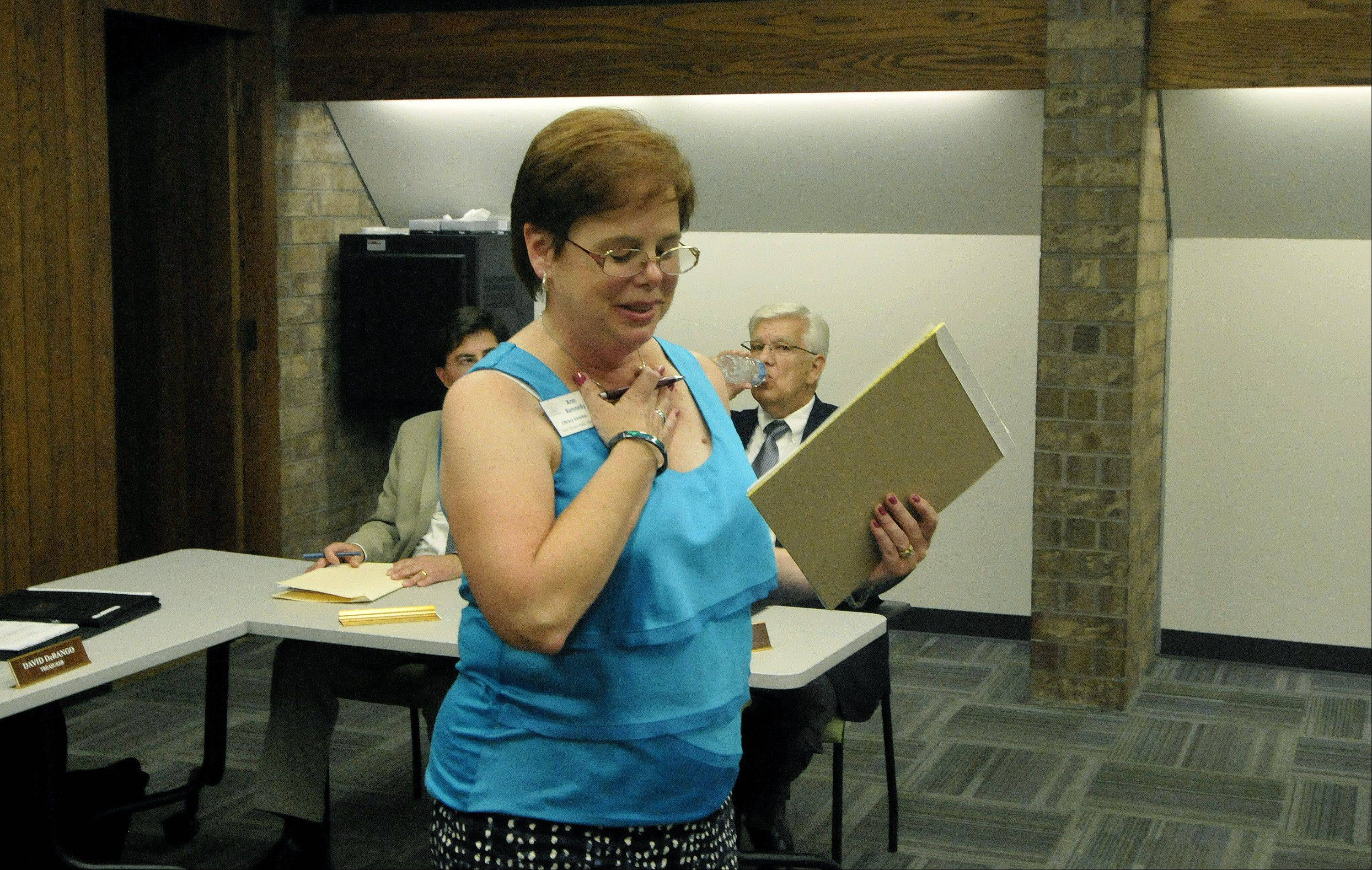 Carol Stream Library Director Ann Kennedy holds back tears as she speaks to a crowd of residents after her firing by the library board Wednesday. The board voted 4-2 to fire her, despite pleas from a packed room of her supporters.