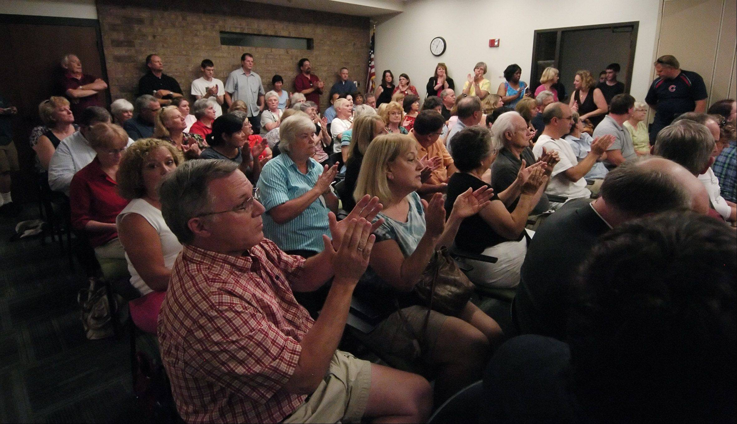 An overflow crowd of Carol Stream residents applaud in support of Library Director Ann Kennedy, who was fired Wednesday night by the library board.
