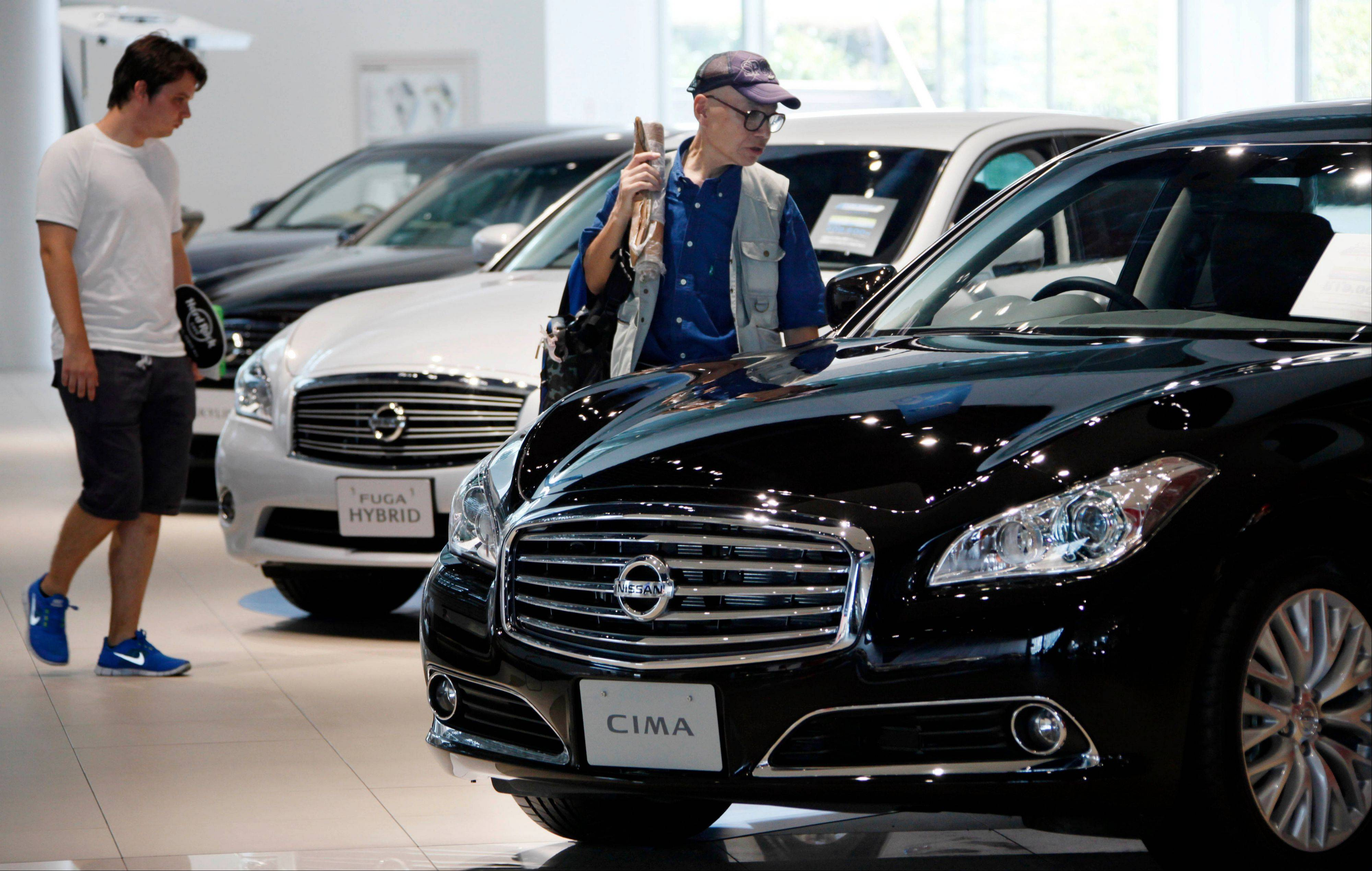Visitors inspect cars at a gallery at the Nissan Motor Co. global headquarters in Yokohama, Thursday.