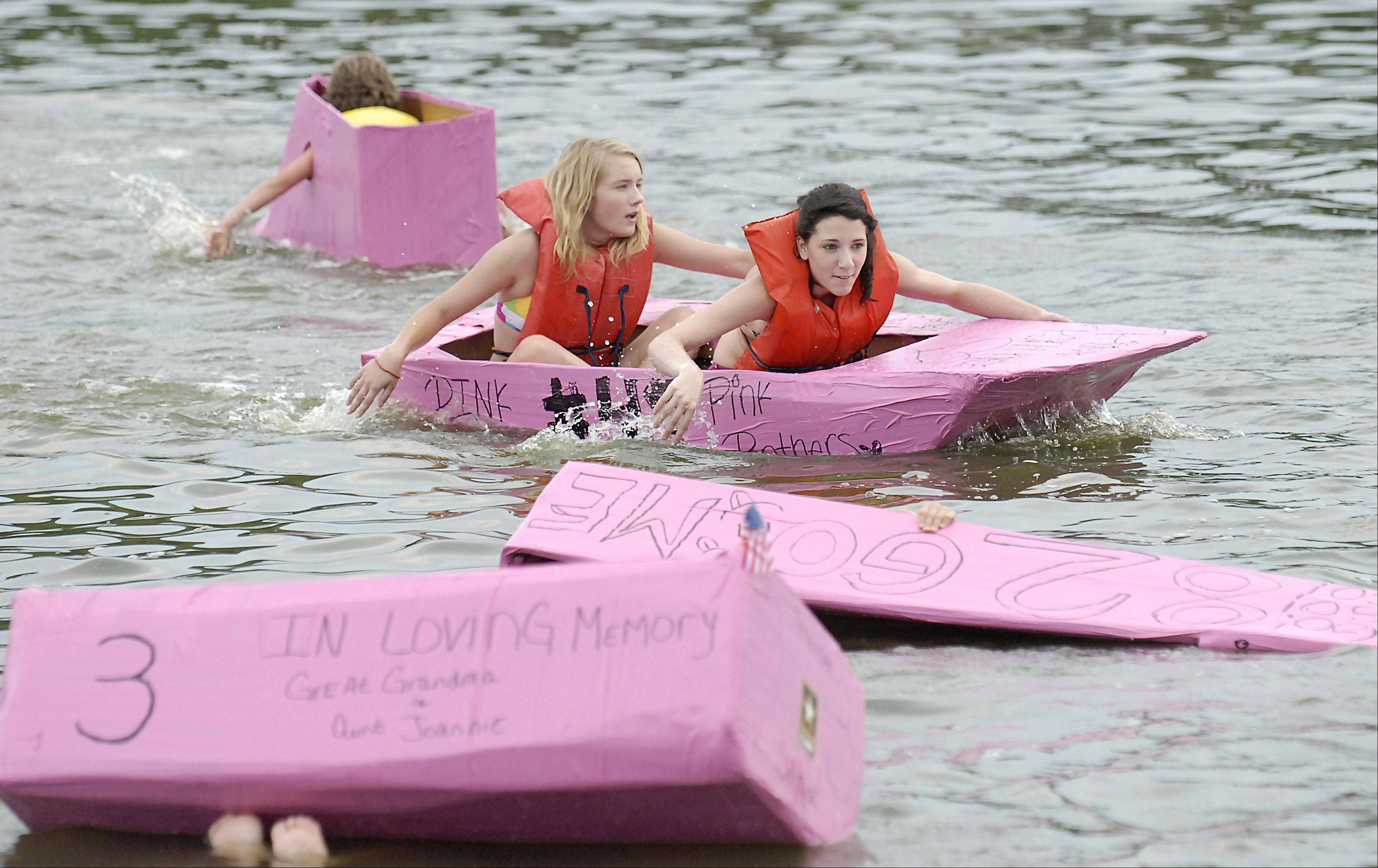 McKenna Moss, left, and Holly Gagliano, both 12 and from Algonquin, make their way through wreckage to be the first place winners in the 12 and under category of the Cardboard Boat Regatta at the 53rd Algonquin Founders� Days on Thursday. This is the fourth year the duo have been in the race.