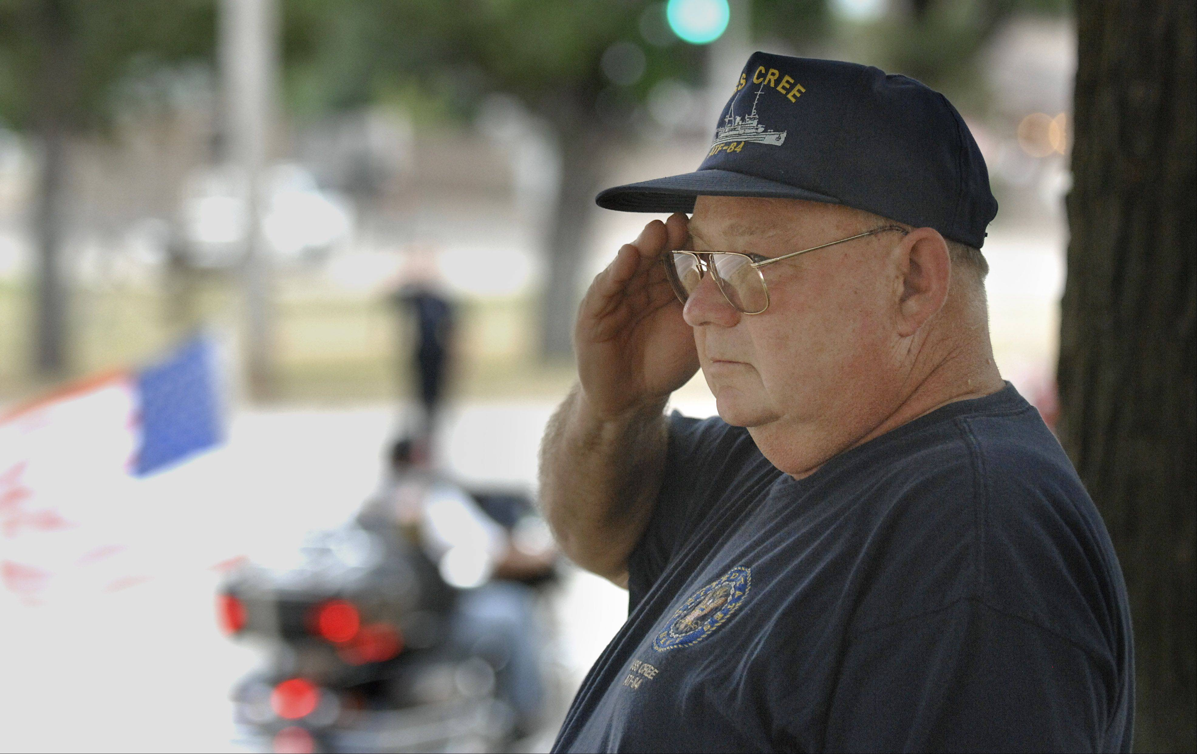 "Bill Keith of Crystal Lake salutes as the hearse of U.S. Navy Petty Officer John Larimer is escorted down Terra Cotta Avenue on the way to Davenport Family Funeral Home Thursday. Keith, a U.S. Navy Vietnam veteran, knew Larimer as a Boy Scout in Troop 168. The onetime assistant scoutmaster remembers Larimer as ""Just a good kid, full of life."""